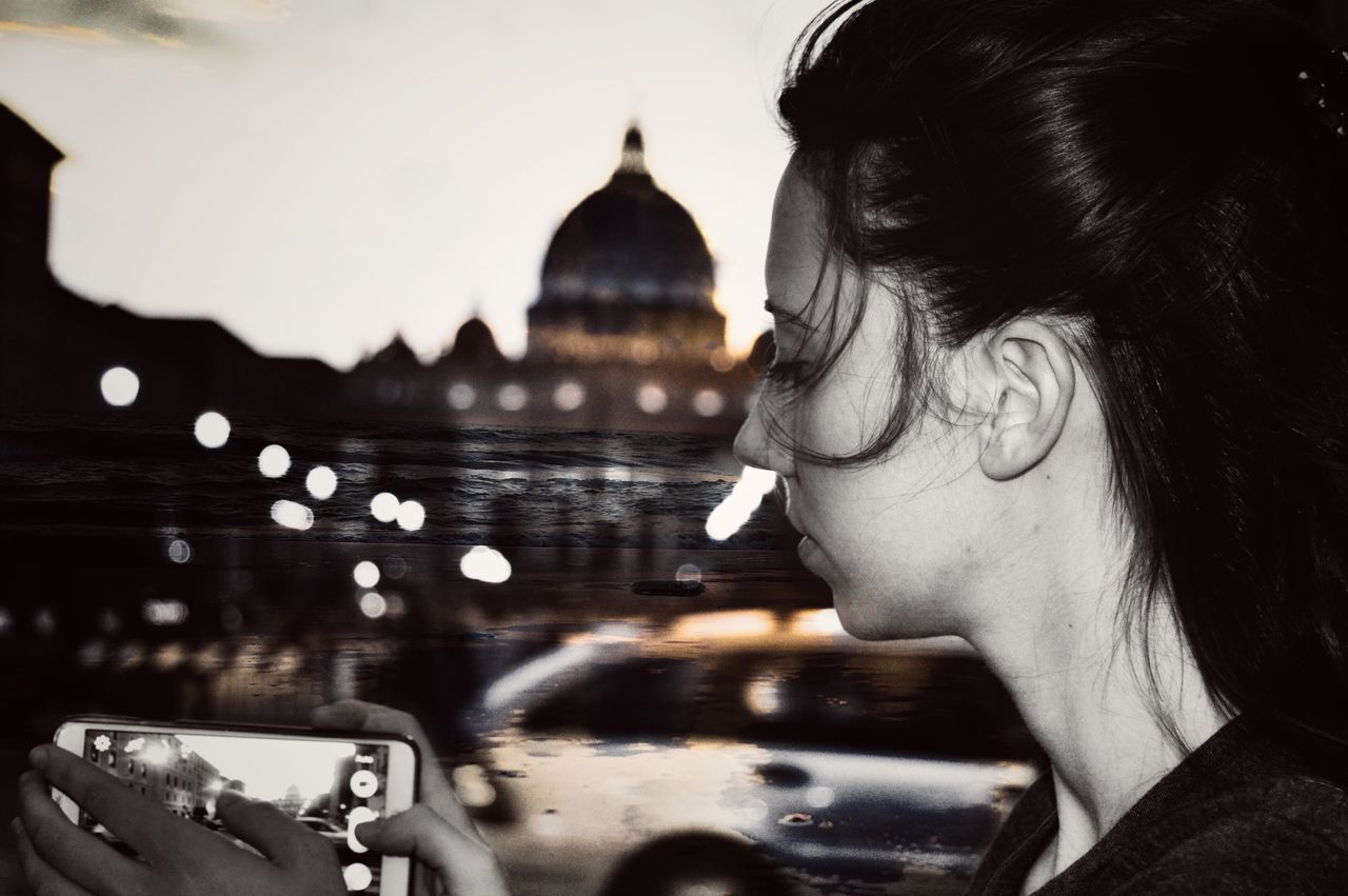 Side View Of Woman Photographing City Through Mobile Phone