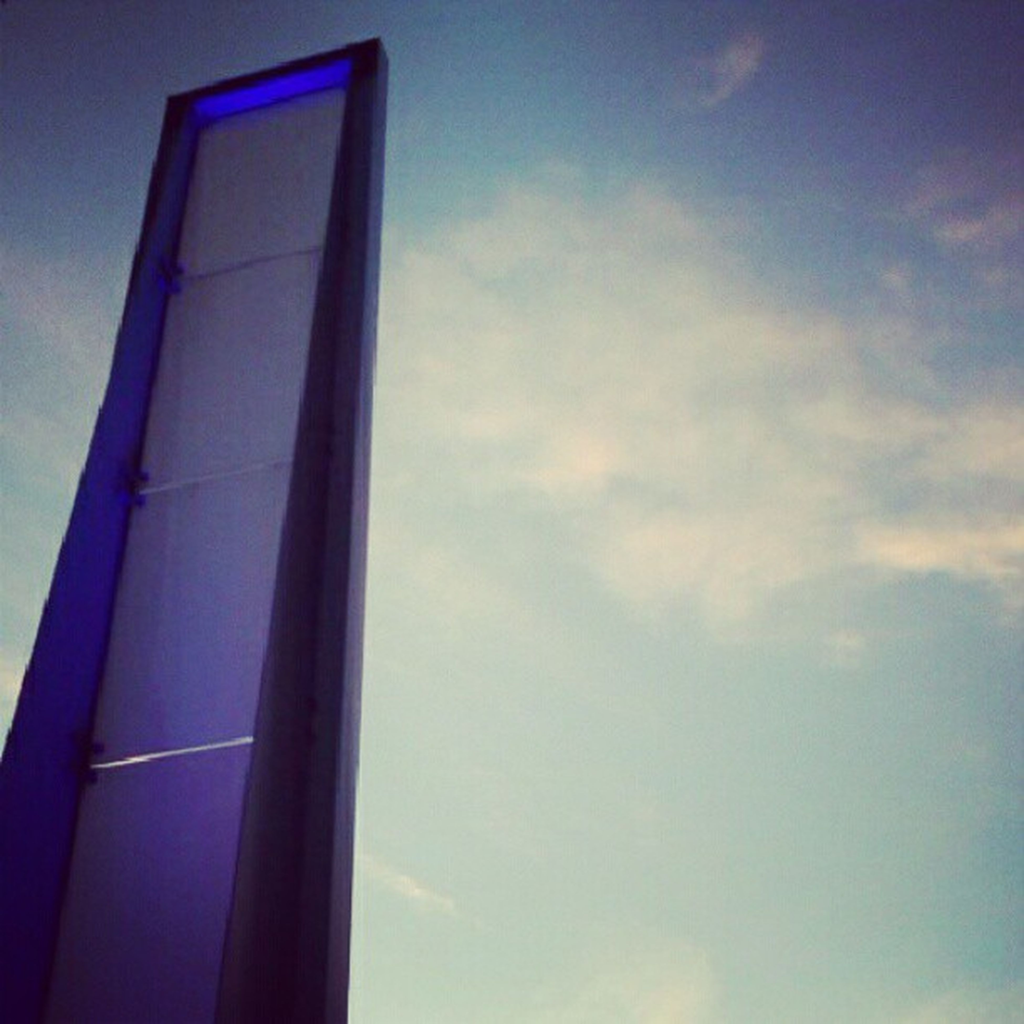 low angle view, sky, architecture, built structure, building exterior, window, cloud - sky, blue, cloud, no people, high section, outdoors, day, building, lighting equipment, cloudy, part of, directly below, sunlight, glass - material