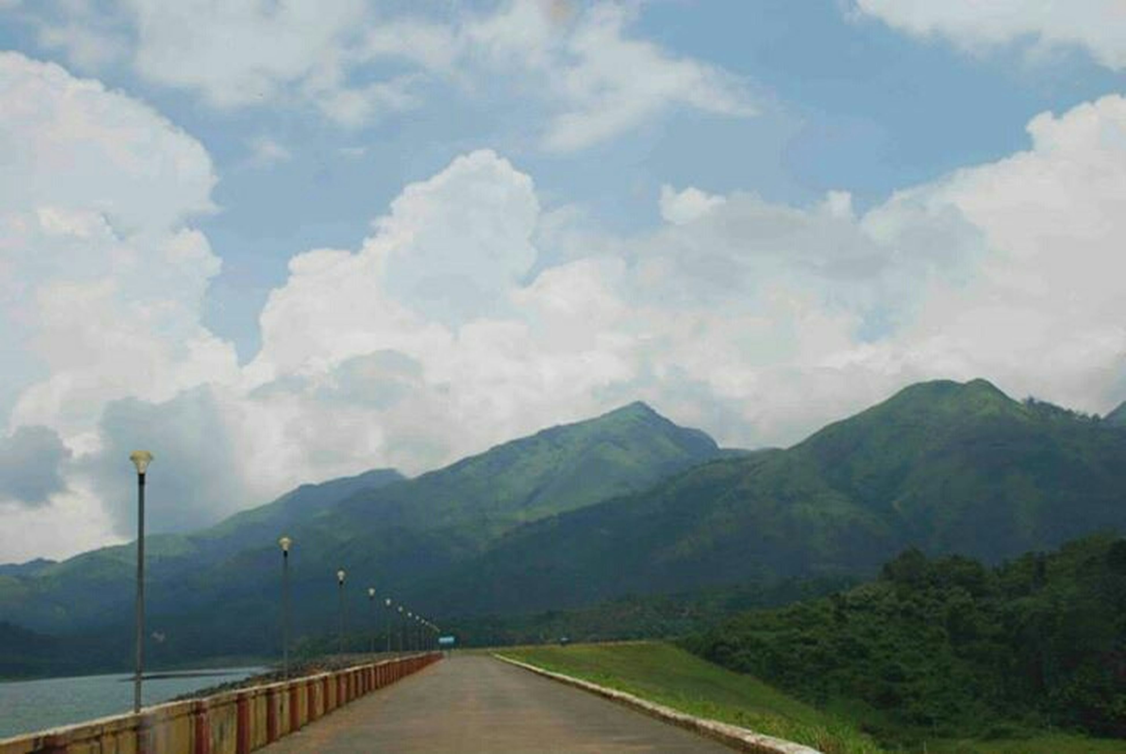 mountain, the way forward, sky, mountain range, tranquility, road, tranquil scene, cloud - sky, railing, scenics, nature, beauty in nature, diminishing perspective, cloudy, landscape, transportation, cloud, vanishing point, empty, non-urban scene