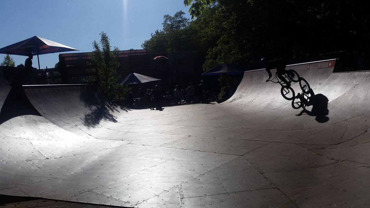 built structure, day, architecture, tree, outdoors, leisure activity, real people, building exterior, skateboard park, sky, nature