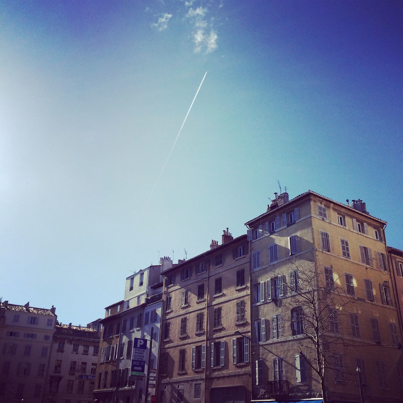 vapor trail, architecture, built structure, building exterior, contrail, no people, sky, low angle view, blue, outdoors, day
