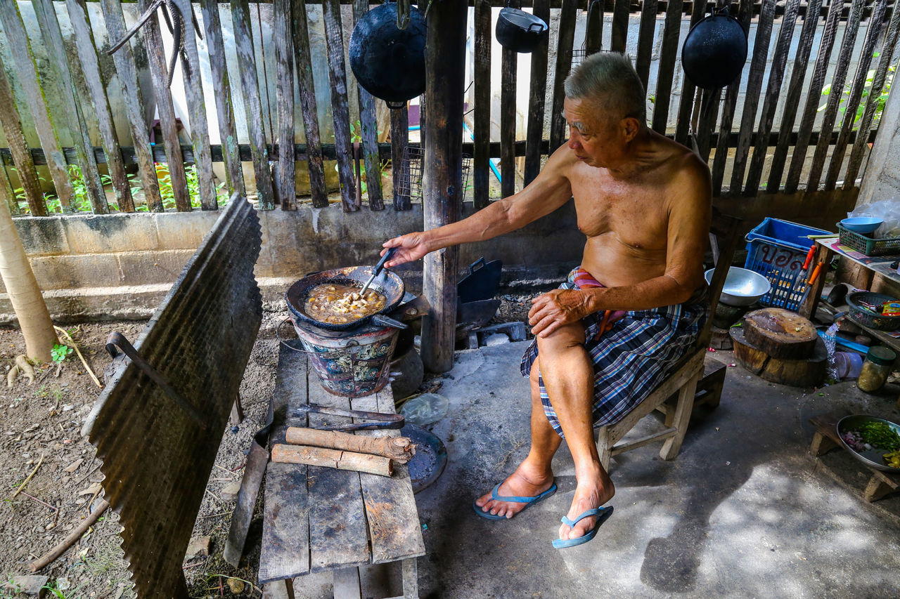 Old men are sitting at home cooking in Ban Hong is a district of Lamphun Province, northern Thailand. Cooking At Home Wait Elderly Man Old People, Man