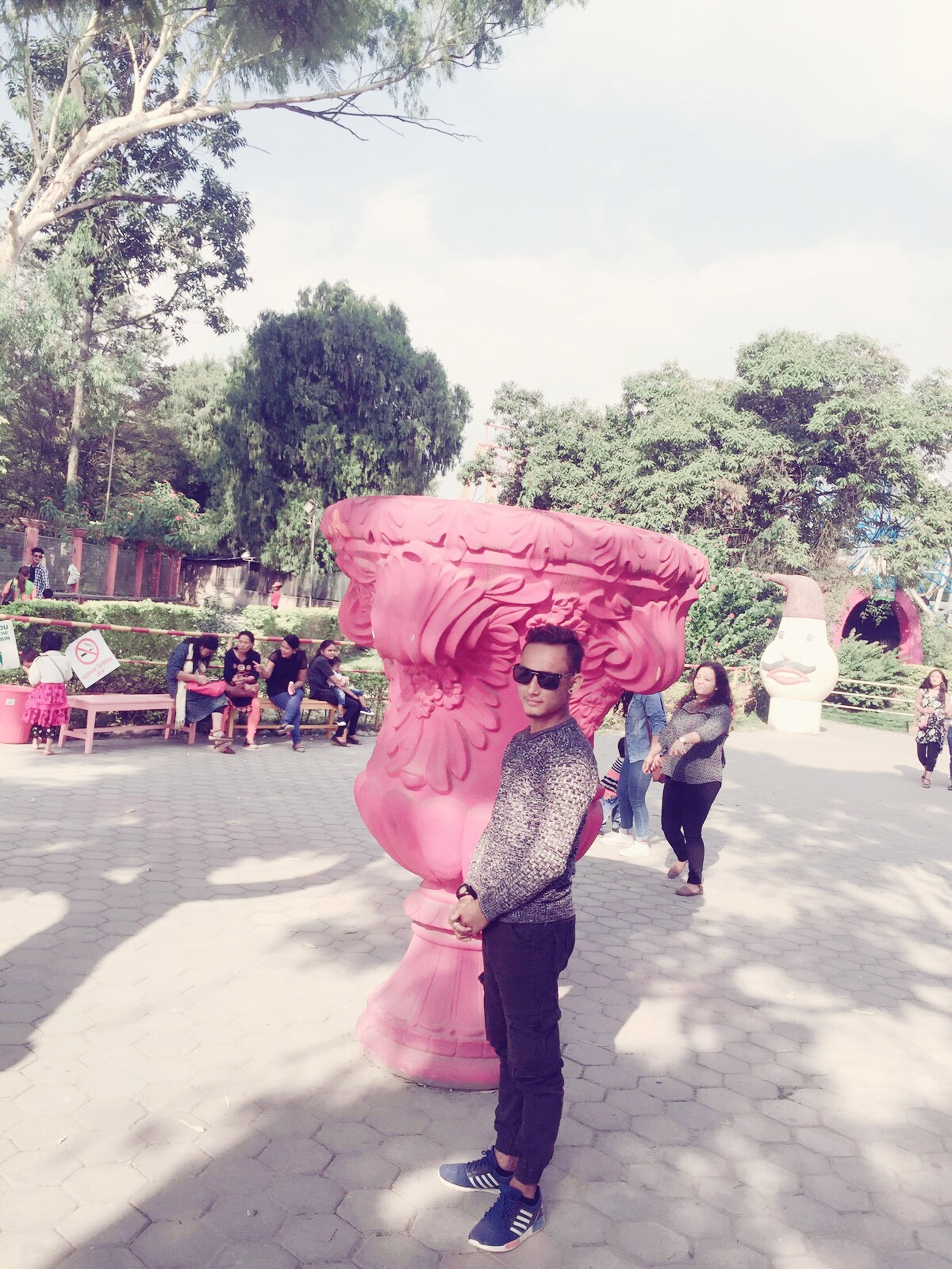tree, one person, full length, pink color, real people, one girl only, happiness, lifestyles, outdoors, day, leisure activity, powder paint, childhood, people, sky, clown, holi, human body part, adult