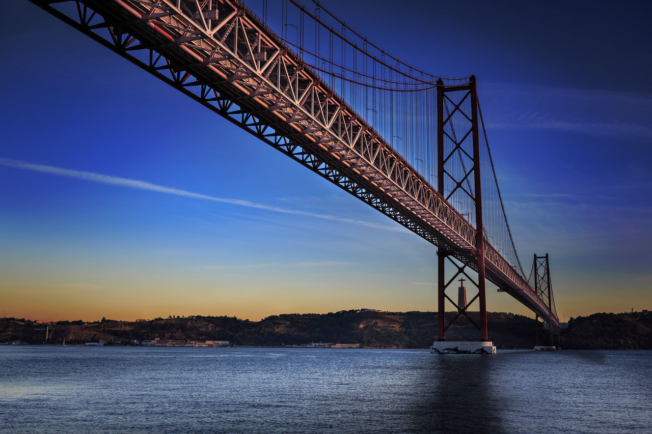 The Ponte 25 de Abril Bridge in Lisbon, Portugal Architecture Bridge - Man Made Structure Built Structure City, Ponte 25 De Abril Bridge, Sintra, Architecture, Atlantic, Blue, Bridge, Coast, Europe, Evening, Famous, Holiday, Landmark, Landscape, Lights, Lisboa, Lisbon, Metal, National, Night, Outdoor, Palace, Park, Portugal, River, Sea, Sky, Summer, Tagus, Tejo, Tourism, Transportation, Travel, View, Water Connection Day Nature No People Outdoors Sky Transportation Water