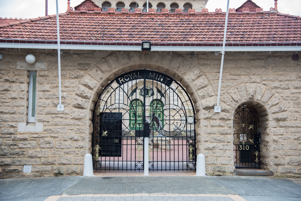 Gated archway entrance of the Perth Mint with limestone architecture and tile roof on cloudy day in Perth, Western Australia. Arch Architecture Archway Brick Building Building Exterior Closed Entrance Façade Finance Front View Gate Gateway Government Historic Limestone Mint Money Perth Perth Mint Roof Terracotta Tile Tourist Attraction  Western Australia