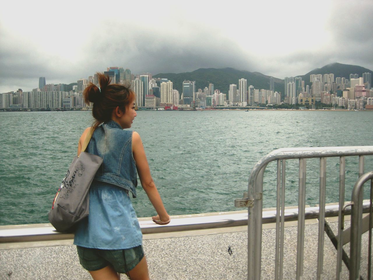 real people, architecture, building exterior, built structure, railing, cityscape, one person, casual clothing, city, outdoors, leisure activity, lifestyles, sky, standing, day, sea, water, mountain, skyscraper, coin-operated binoculars, young adult, nature