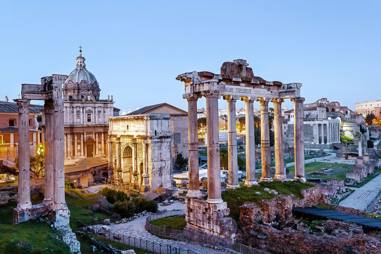 The Roman Forum photographed at sunset, with artificial lights on. The Roman Forum: Left the Temple of Vespasian, the Arch of Septimius Severus and the Temple of Saturn. Rightmost the plaza of the Basilica Giulia front of the three columns of the Temple of Castor and Pollux and the Palatine Hill. Ancient Architecture Building Capitoline Church Civilization Columns Fororomano Historic Italian Landmark Old Ornate Panorama Roman Roman Forum Ruins Temple Traditional