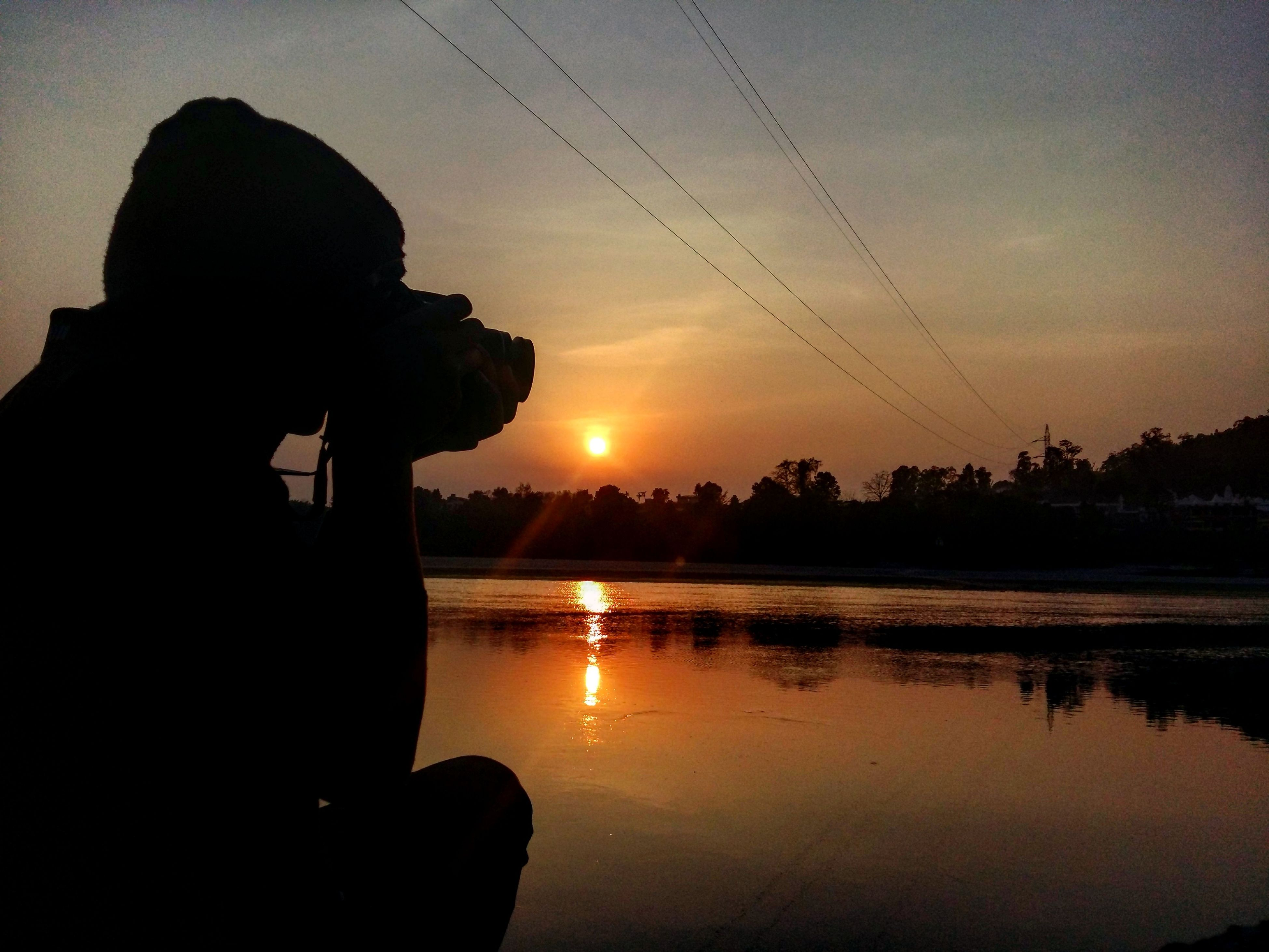sunset, silhouette, sun, water, scenics, orange color, reflection, tranquility, sky, tranquil scene, beauty in nature, idyllic, nature, sea, lake, one person, sunlight, outdoors, calm, outline