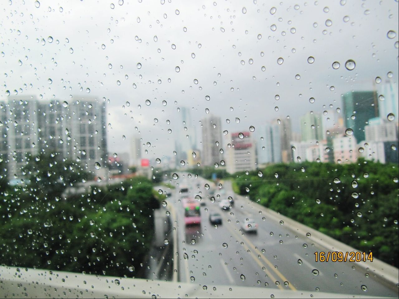 drop, glass - material, architecture, built structure, raindrop, window, building exterior, water, no people, wet, city, transportation, day, skyscraper, land vehicle, outdoors, road, sky, cityscape, nature, close-up