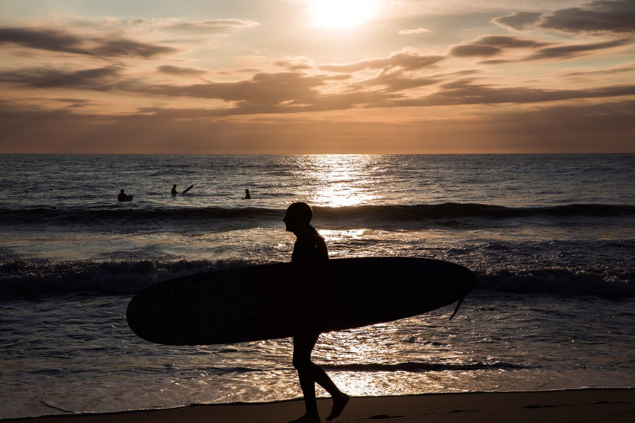 sunset, sea, silhouette, water, nature, beauty in nature, scenics, horizon over water, real people, sky, orange color, standing, beach, tranquility, leisure activity, tranquil scene, sun, sunlight, lifestyles, one person, outdoors, skill, men, vacations, extreme sports, wave, paddleboarding, day, people