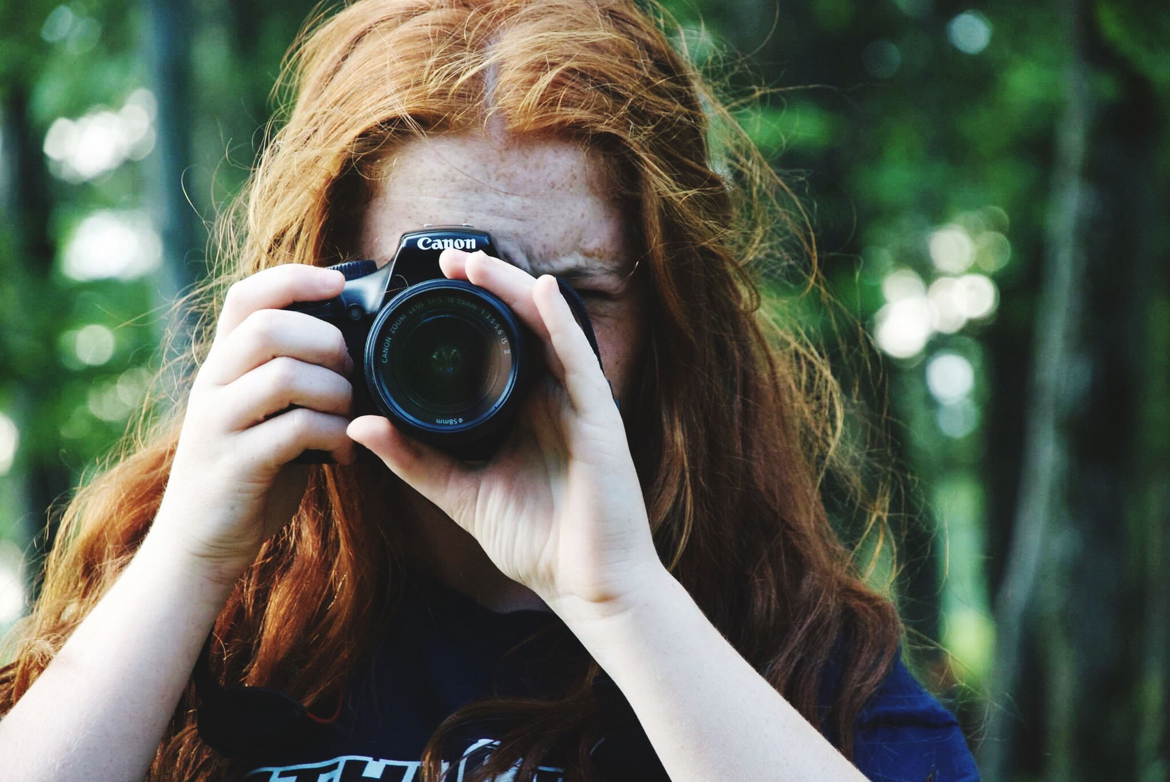 close-up, leisure activity, lifestyles, focus on foreground, person, headshot, holding, camera - photographic equipment, outdoors, day, human face, human eye, human hair, hiding, looking