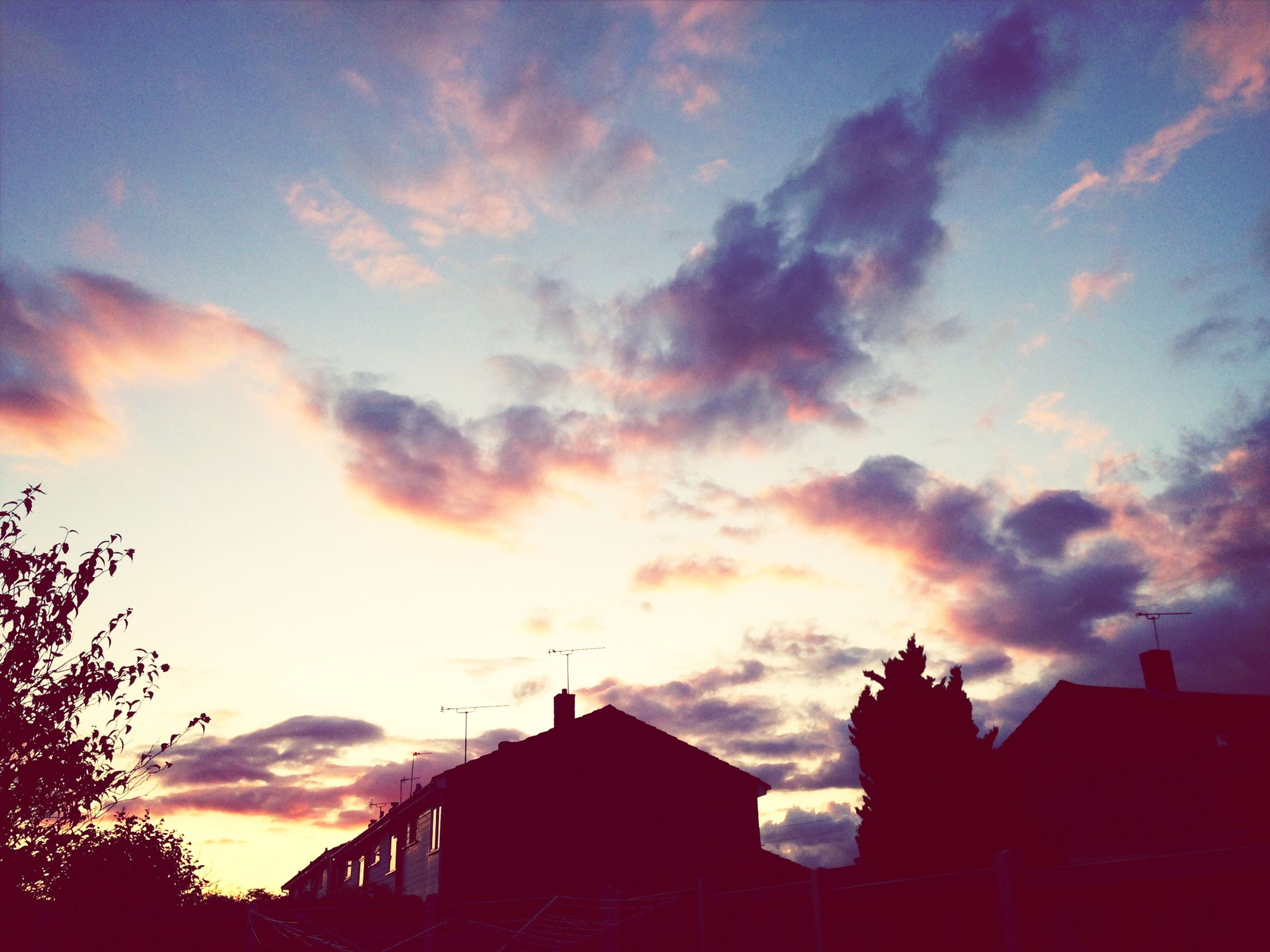 building exterior, architecture, built structure, sunset, sky, cloud - sky, low angle view, silhouette, house, cloudy, residential structure, cloud, orange color, high section, residential building, building, dramatic sky, roof, outdoors, nature