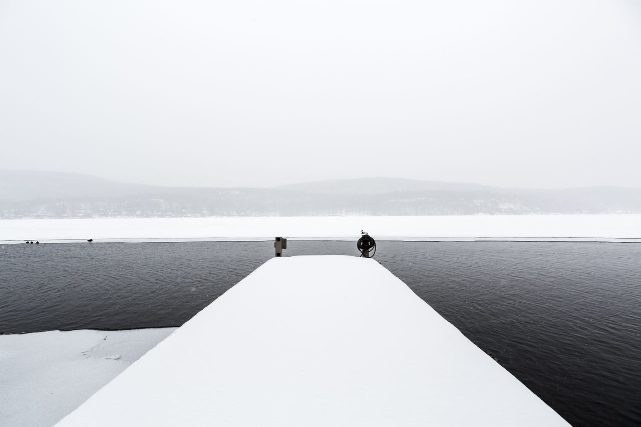 Snow Covered Pier By Lake Against Sky