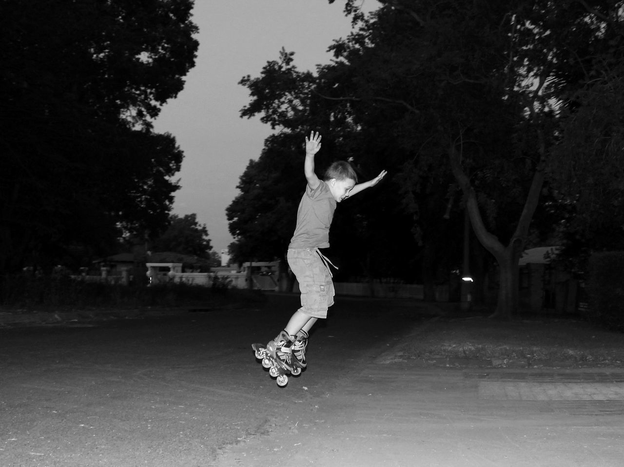 Boy Jumping While Roller Skating On Road At Night