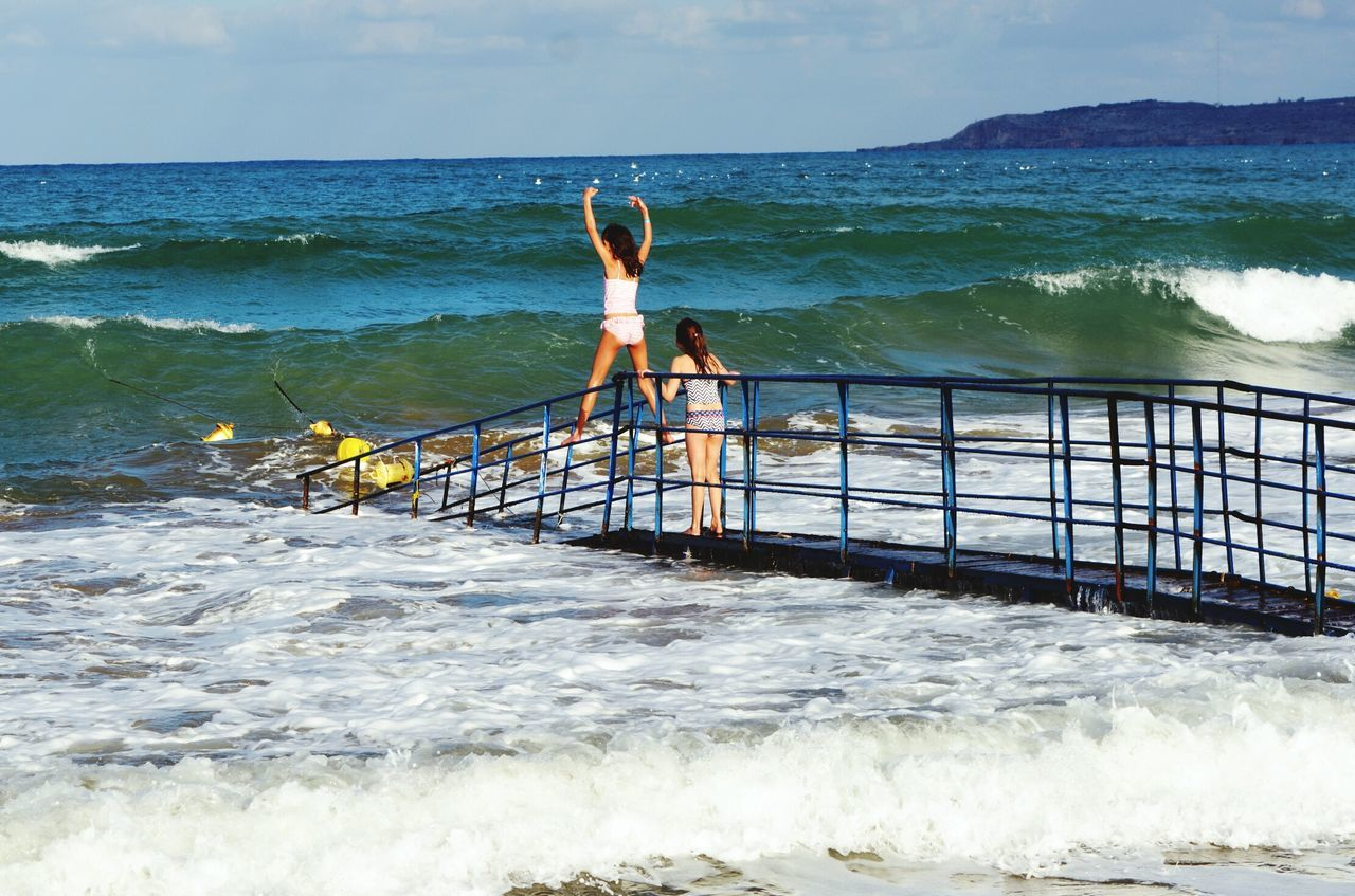 Sea Water Wave Beach Outdoors Agility Full Length Beauty In Nature Young Adult Challenge Nature Adult Sky People Kids Travel Destinations Beach Life Beach Day Sand & Sea Standing Tall Waves Breaking On A Shore Crete Greece Bridge Brave brave girls