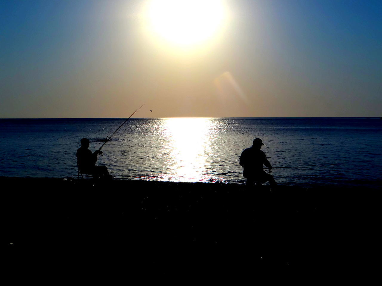 sea, silhouette, horizon over water, water, sun, fishing, nature, sunset, scenics, real people, two people, fishing pole, beauty in nature, tranquil scene, tranquility, clear sky, weekend activities, leisure activity, outdoors, standing, men, sunlight, sky, beach, day, people