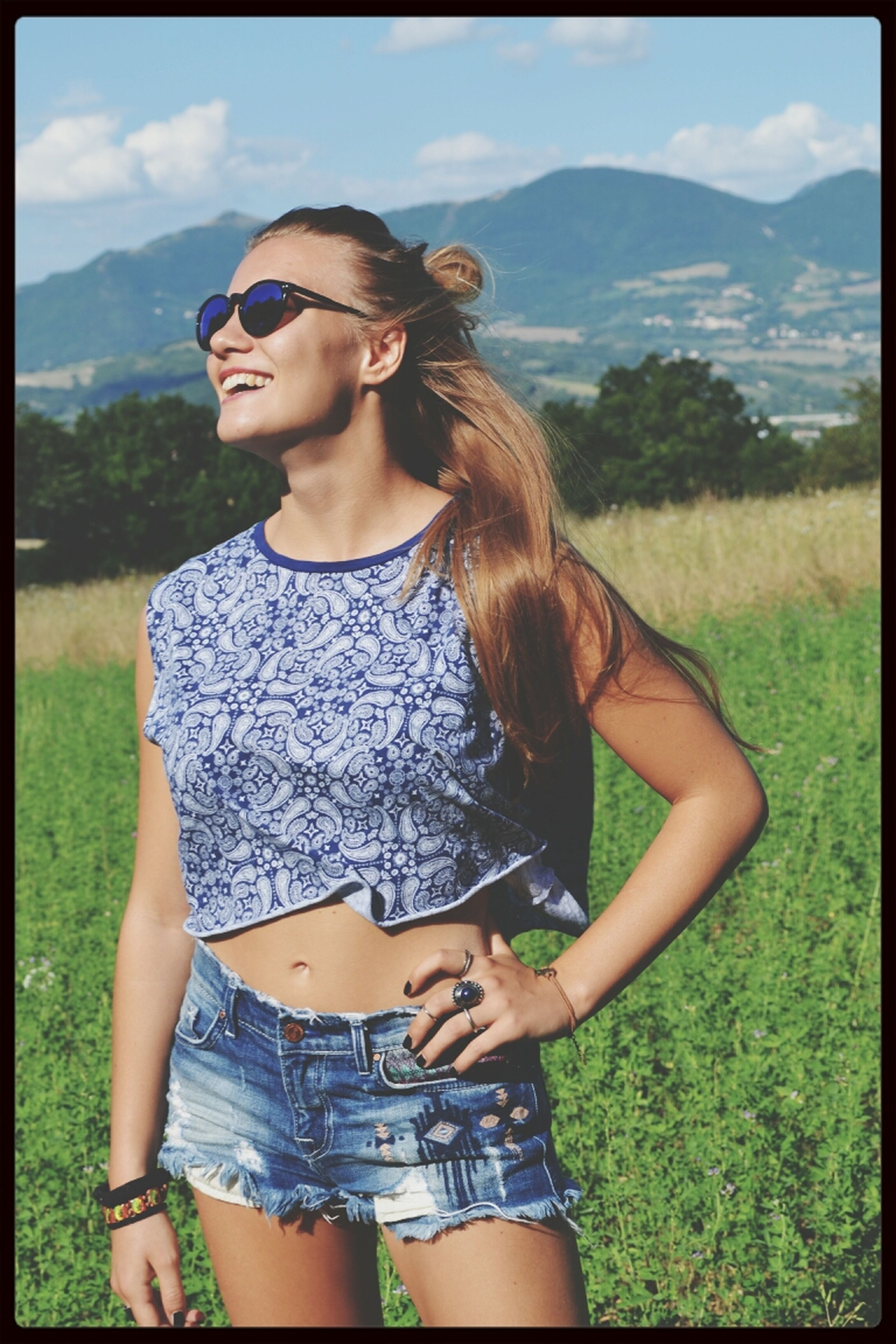 young adult, person, transfer print, young women, lifestyles, grass, looking at camera, sky, portrait, leisure activity, mountain, casual clothing, auto post production filter, field, smiling, front view, sunglasses