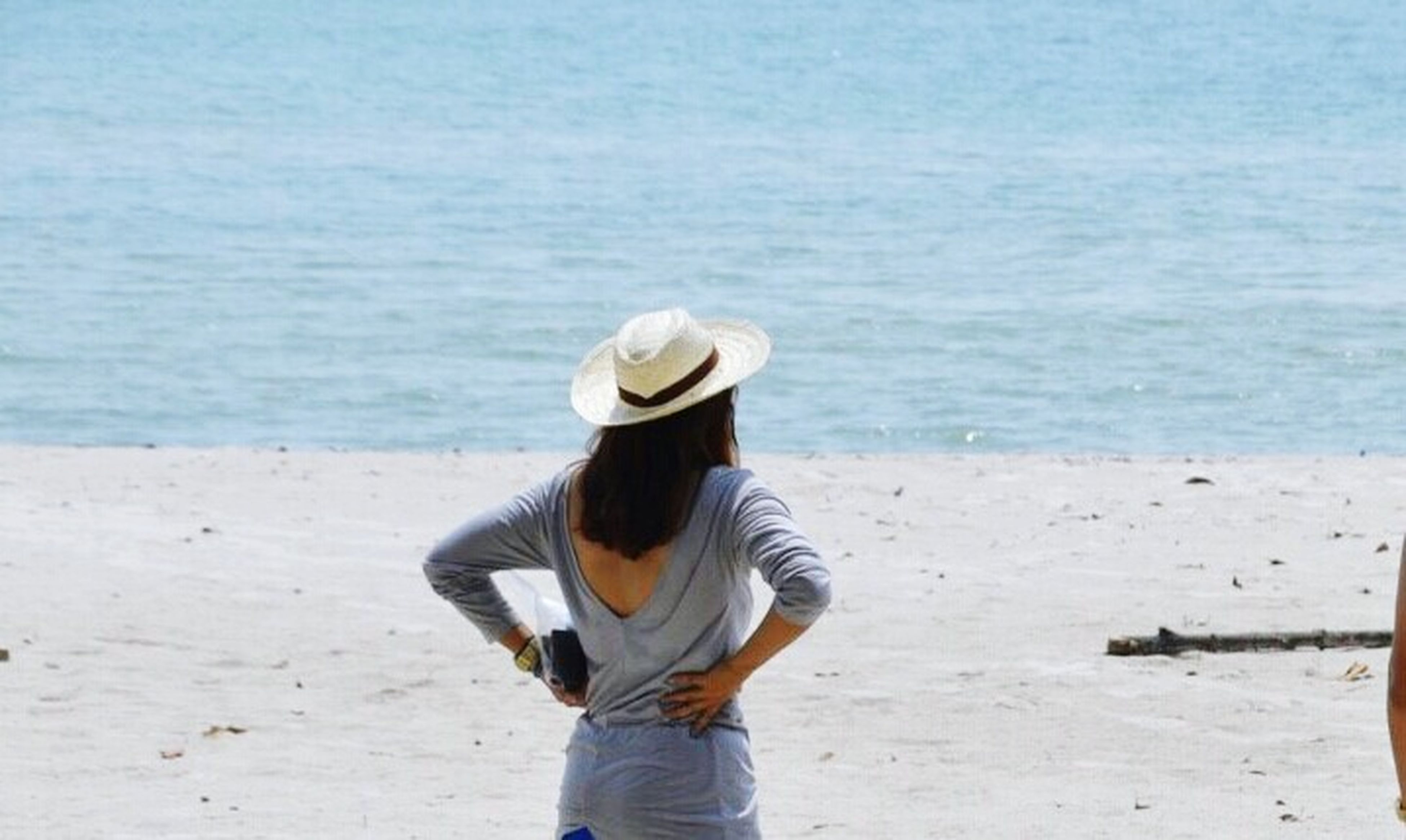 beach, sea, water, lifestyles, shore, rear view, leisure activity, casual clothing, sand, horizon over water, standing, three quarter length, tranquility, vacations, hat, full length, tranquil scene, day