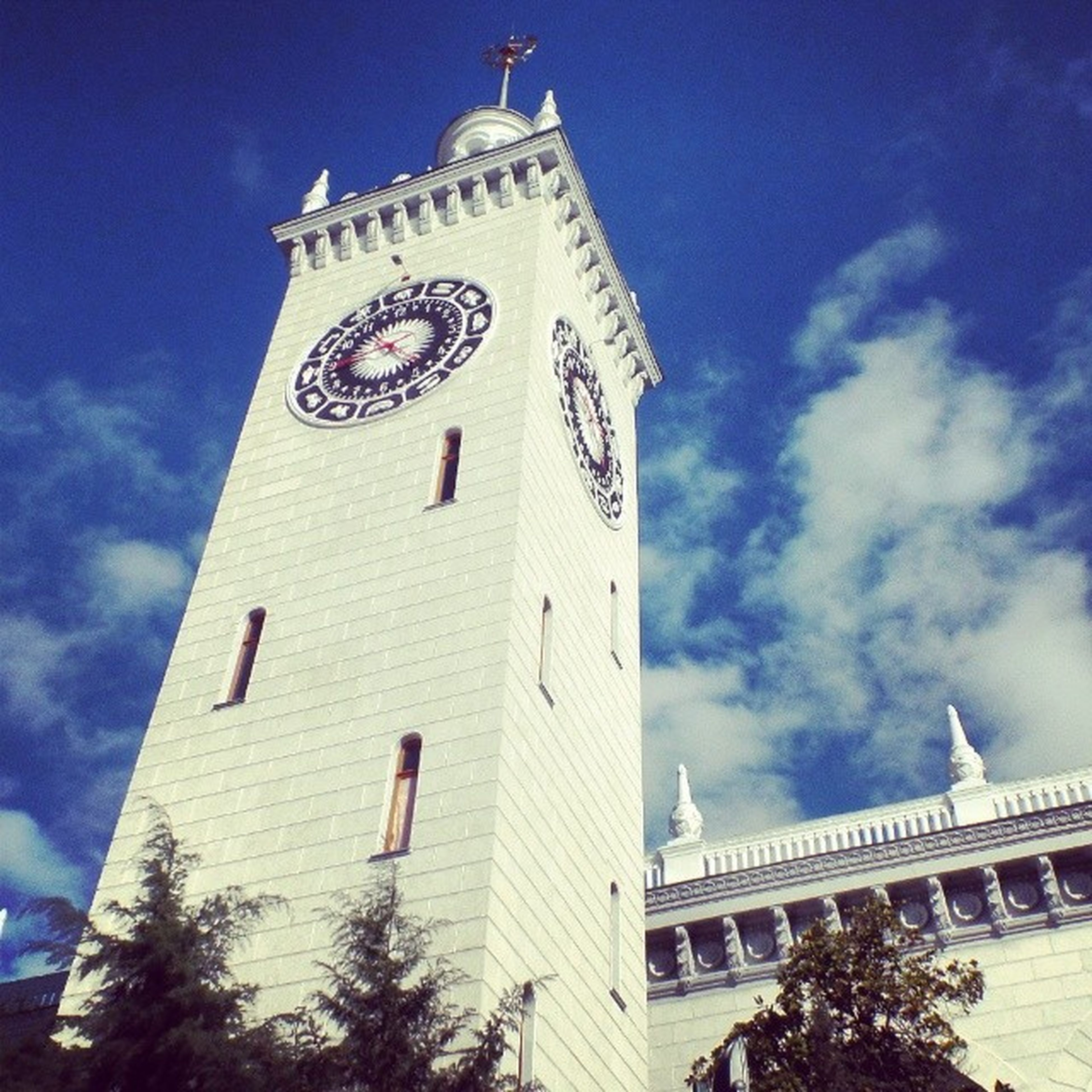 architecture, built structure, building exterior, low angle view, clock tower, tower, sky, religion, church, place of worship, tall - high, famous place, travel destinations, spirituality, clock, city, cloud - sky, flag