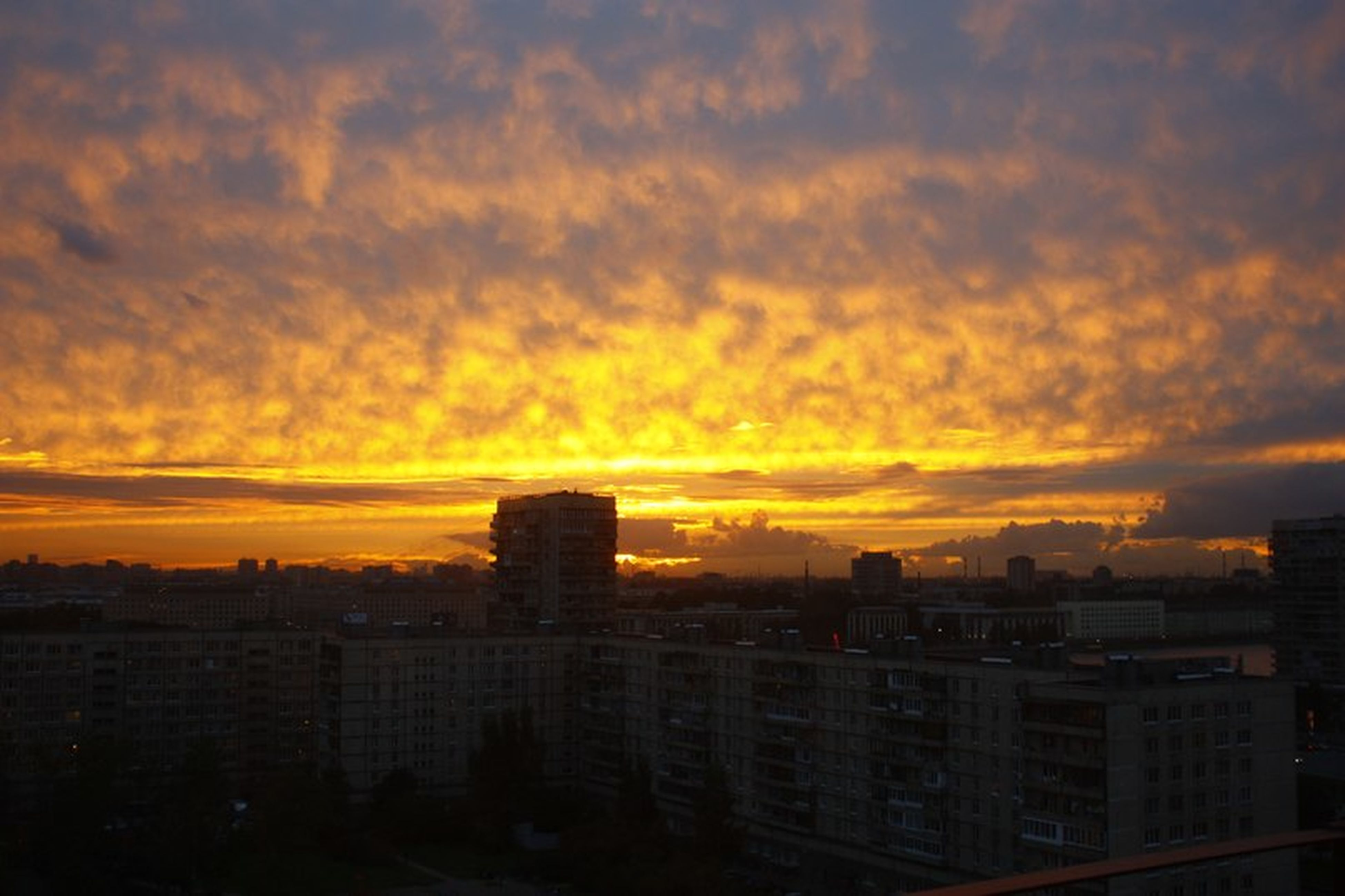 sunset, building exterior, architecture, built structure, city, orange color, sky, cityscape, cloud - sky, residential building, residential district, cloudy, cloud, residential structure, silhouette, city life, dramatic sky, skyscraper, high angle view, outdoors