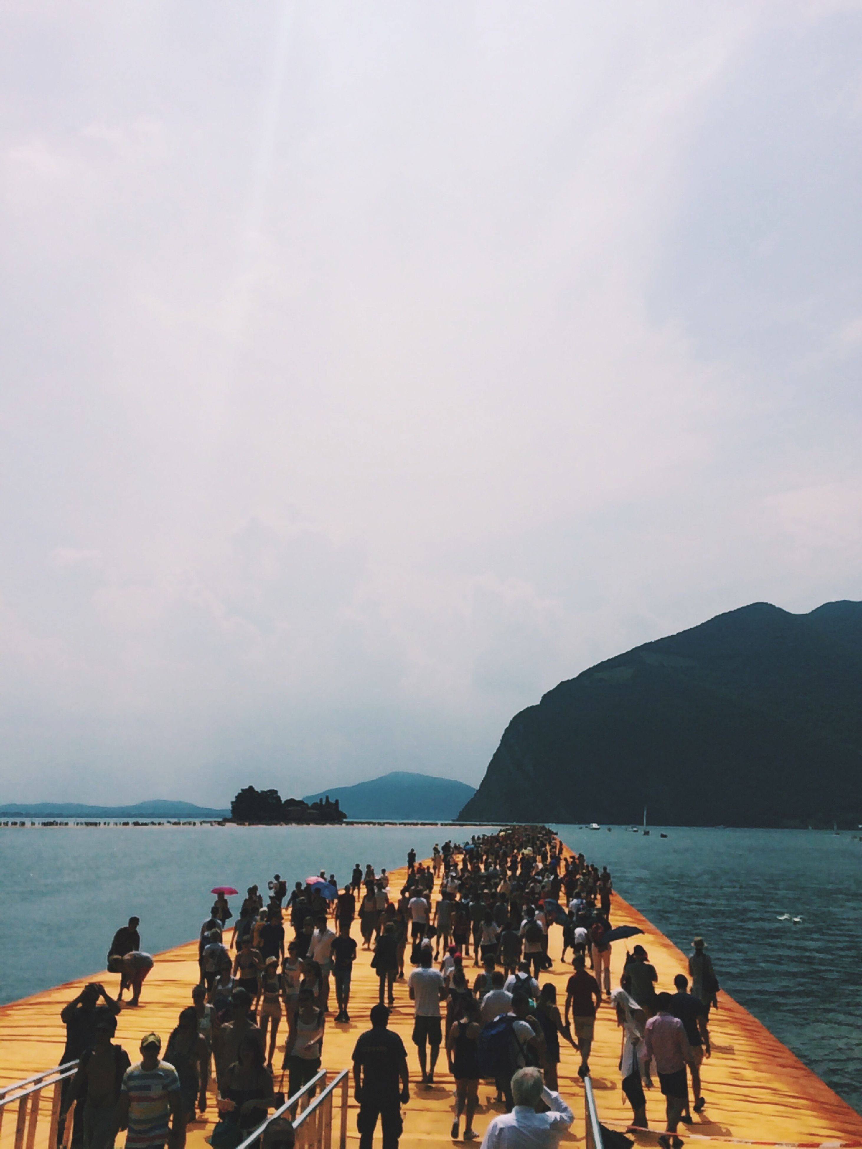 water, sea, large group of people, sky, person, lifestyles, men, leisure activity, mountain, vacations, tourist, beach, mixed age range, scenics, nature, cloud - sky, outdoors, day, beauty in nature