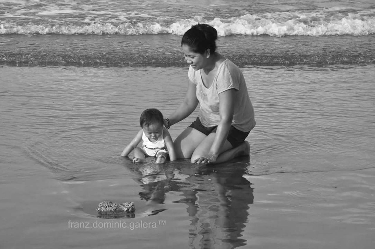 water, childhood, child, girls, casual clothing, lake, full length, beach, two people, real people, lifestyles, portrait, outdoors, sand, wave, bonding, swimming, togetherness, day, people, adult
