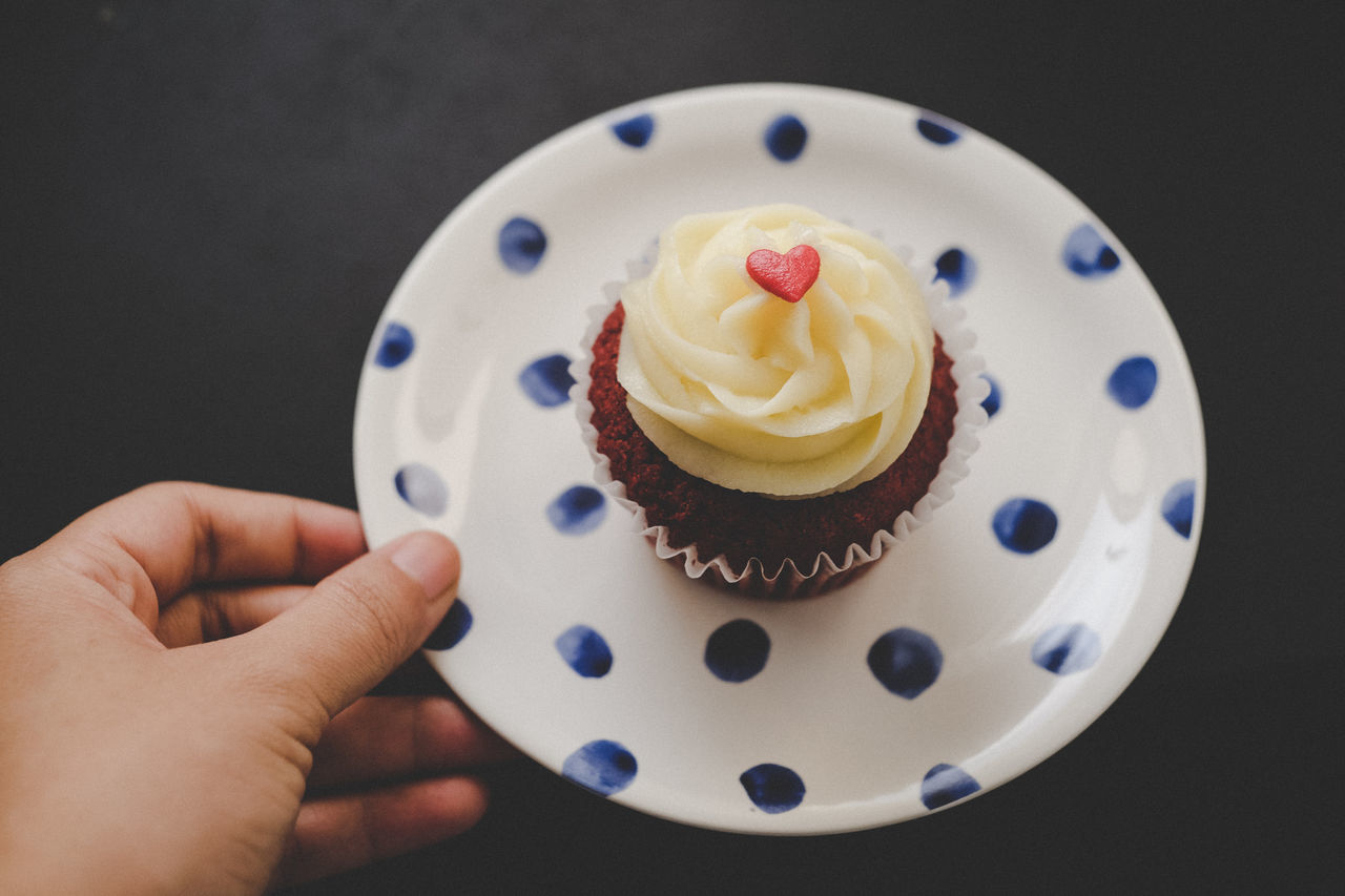 Cropped Image Of Hand Holding Cupcake Plate