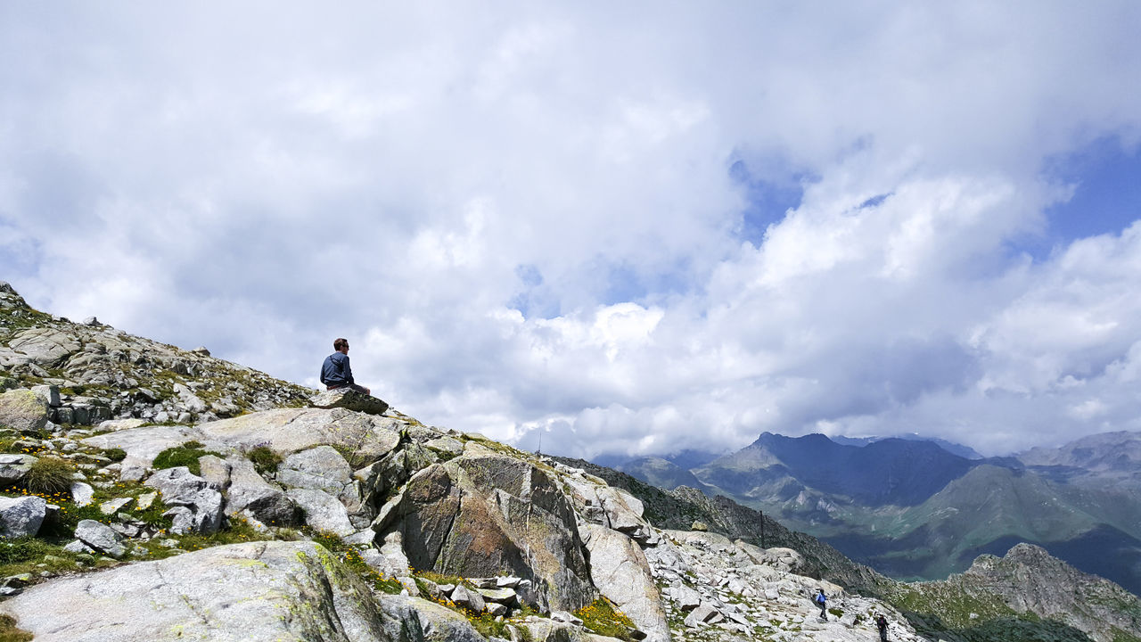 Man Sitting On Cliff Against Sky