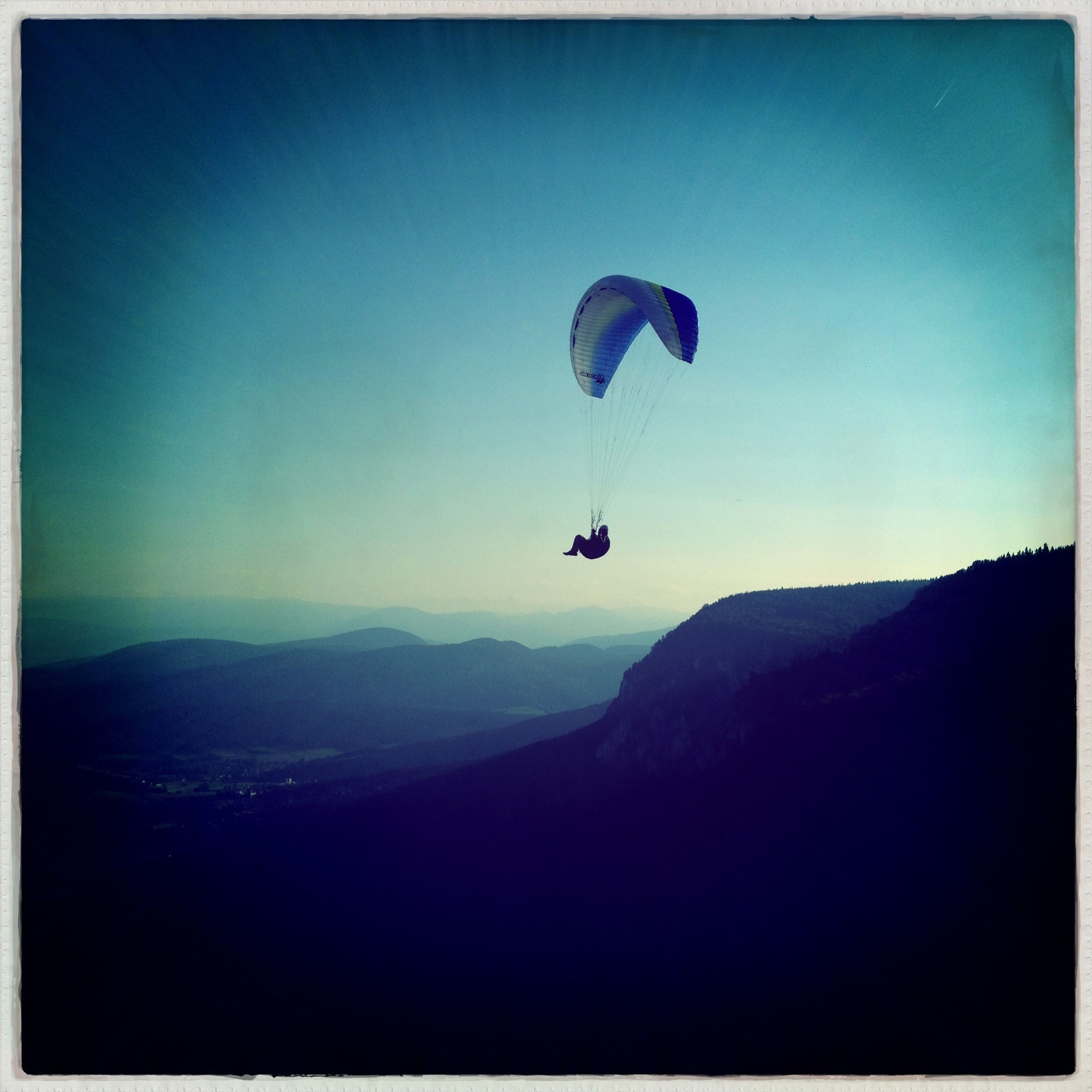mountain, mid-air, extreme sports, adventure, flying, parachute, paragliding, leisure activity, clear sky, scenics, blue, copy space, tranquil scene, lifestyles, tranquility, transportation, sport, mountain range