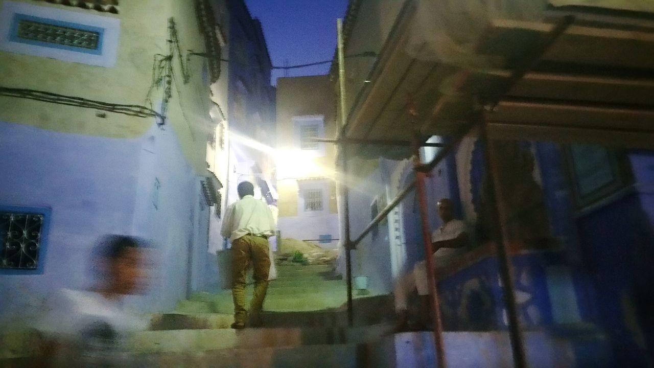 Illuminated Architecture Built Structure Men Building Exterior Lifestyles Residential Building Standing Leisure Activity Walking Street City City Life Full Length Night Person Alley Footpath Old Buildings Blue Walls Blurred Motion Blurred Perspective Perspective Motion Capture Architectural Detail