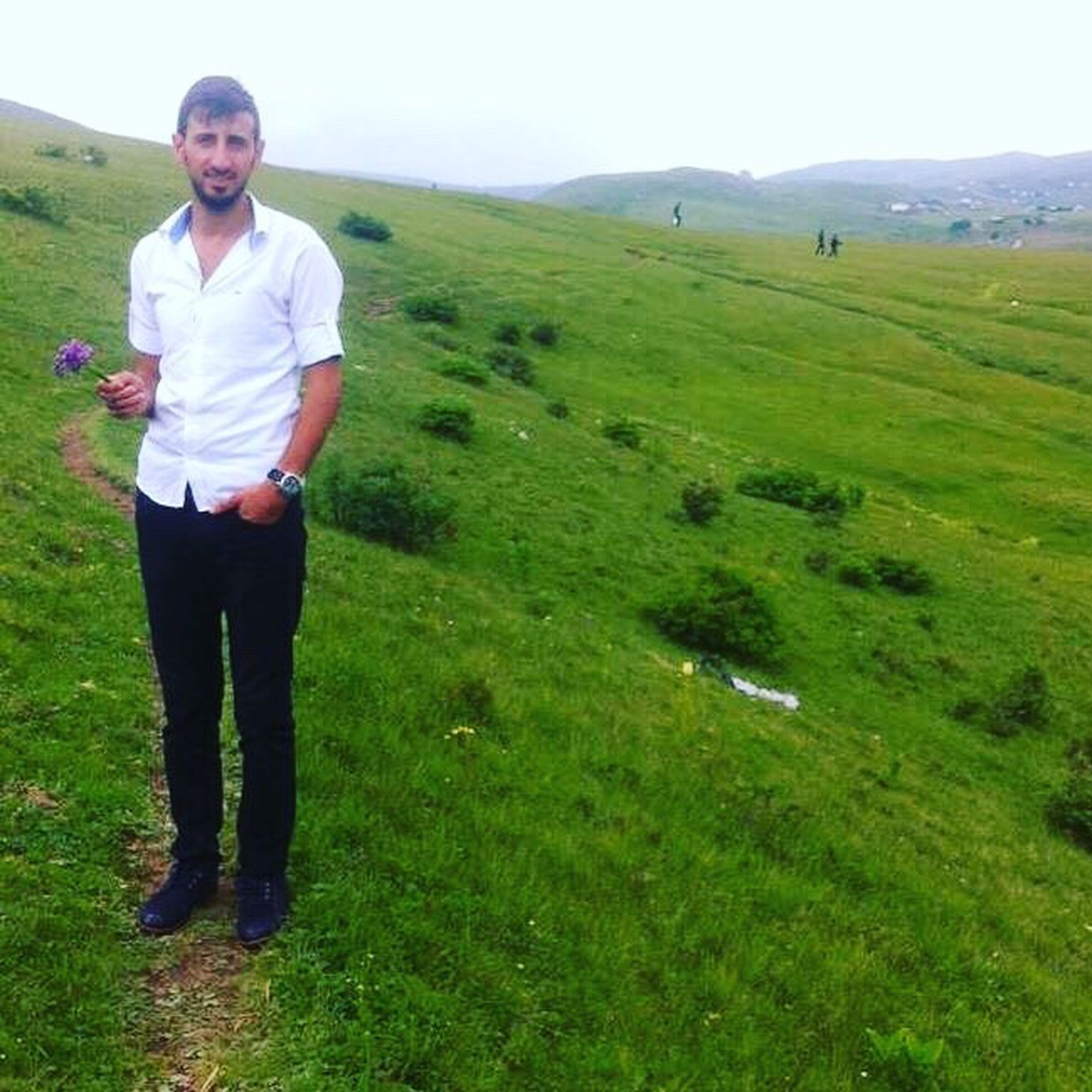 full length, grass, young adult, casual clothing, leisure activity, young men, lifestyles, mountain, green color, person, nature, tranquil scene, tourism, tranquility, t-shirt, vacations, tourist, scenics, beauty in nature, non-urban scene, getting away from it all, remote, outdoors
