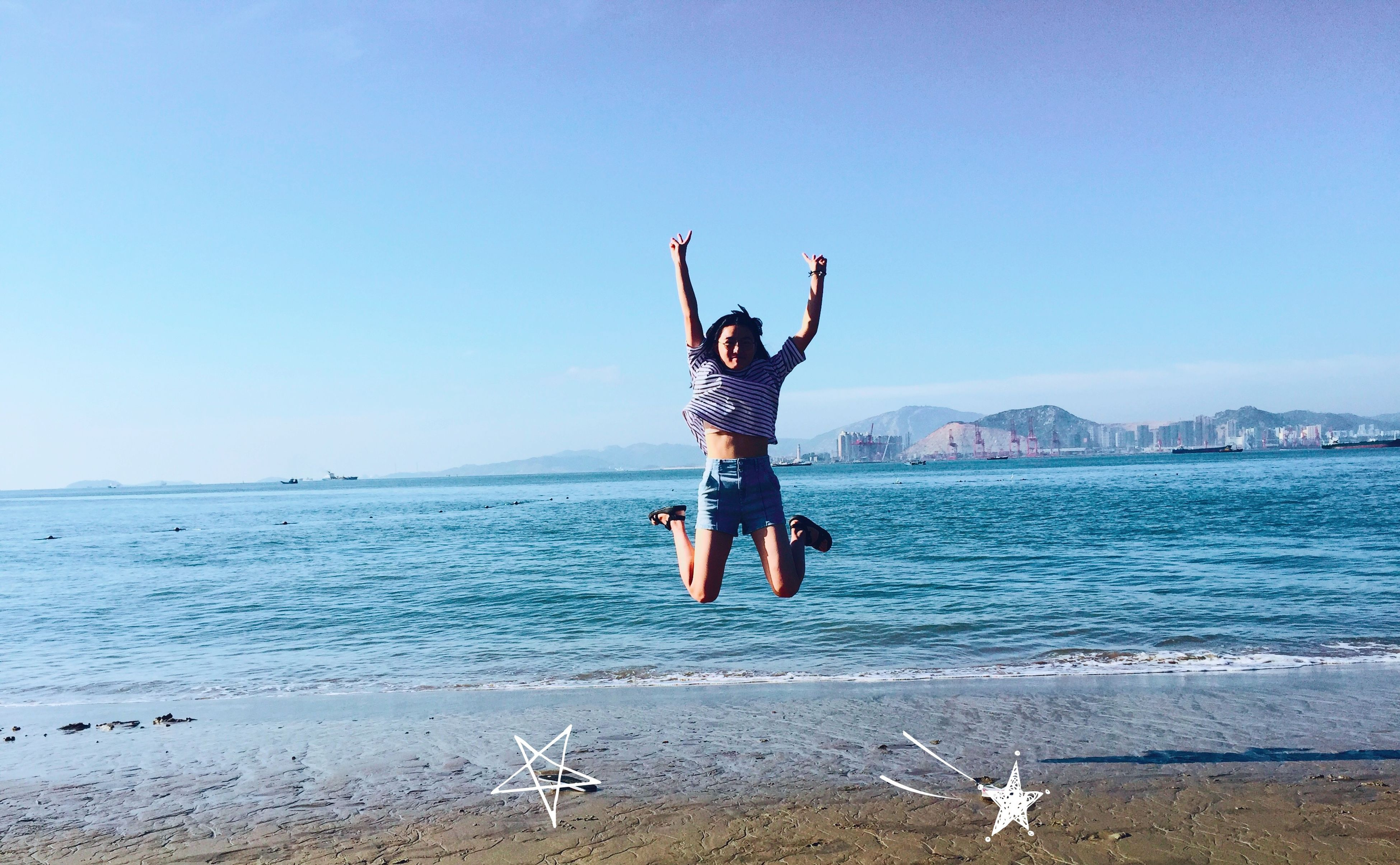 water, sea, clear sky, beach, full length, copy space, lifestyles, leisure activity, shore, vacations, blue, young adult, enjoyment, fun, sand, jumping, mid-air, standing