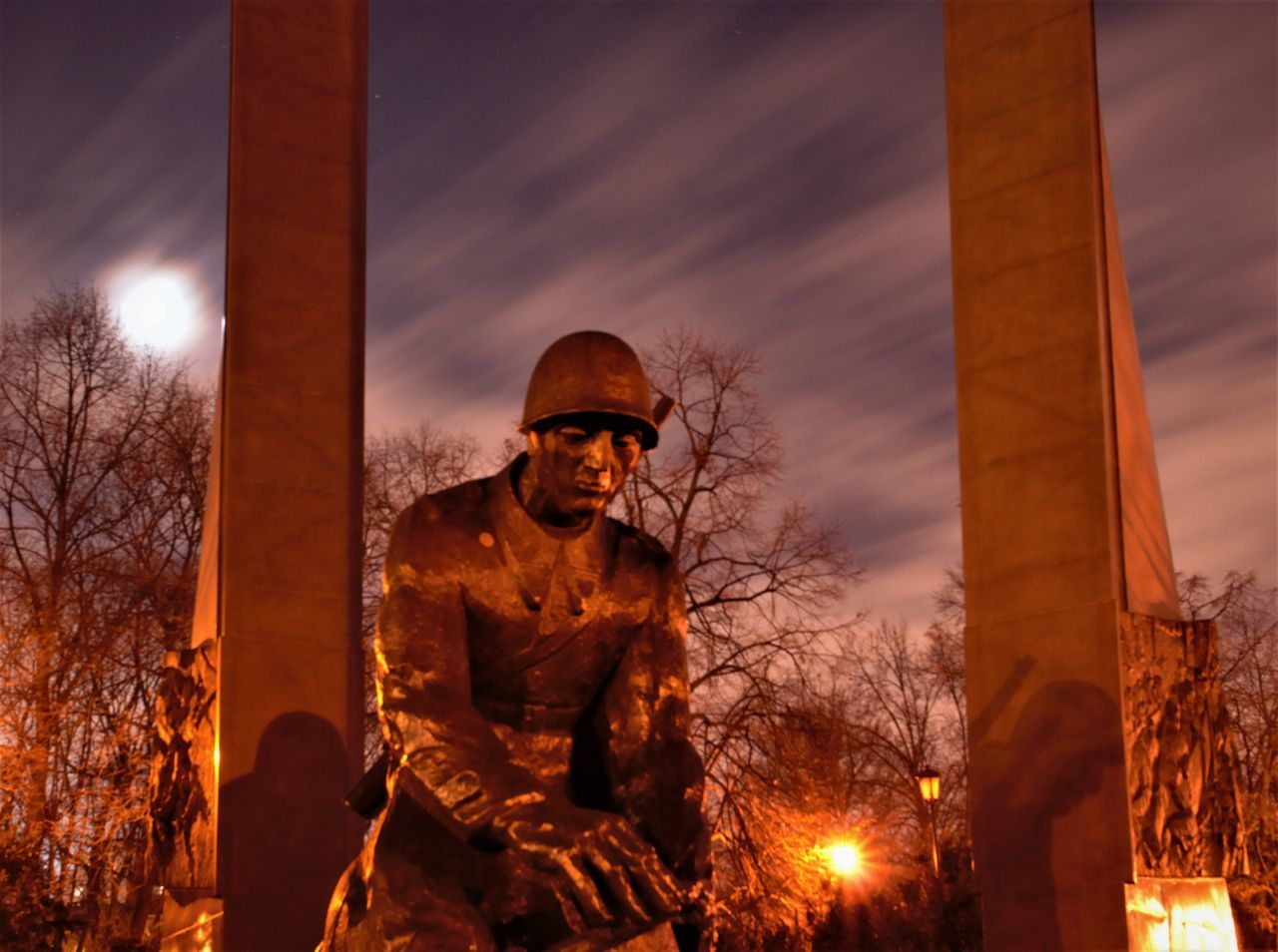 architectural column, statue, real people, religion, architecture, sky, built structure, sculpture, sunset, night, outdoors, tree, standing, army soldier, one person, illuminated, nature