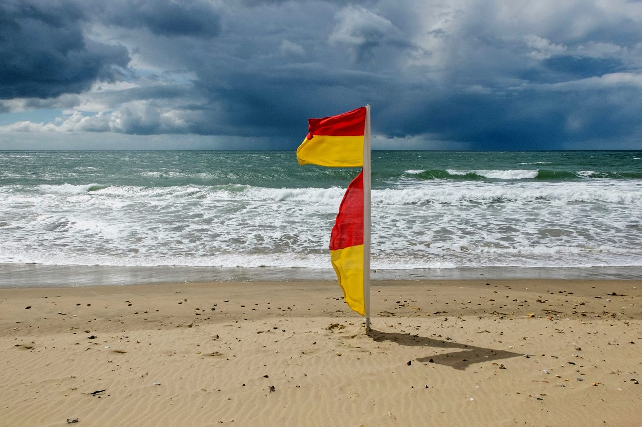 The wonders of the light directly before a storm. RNLI beach flags at Fisherman's Walk. Fujifilm Bournemouth Beach Photography Out Walking