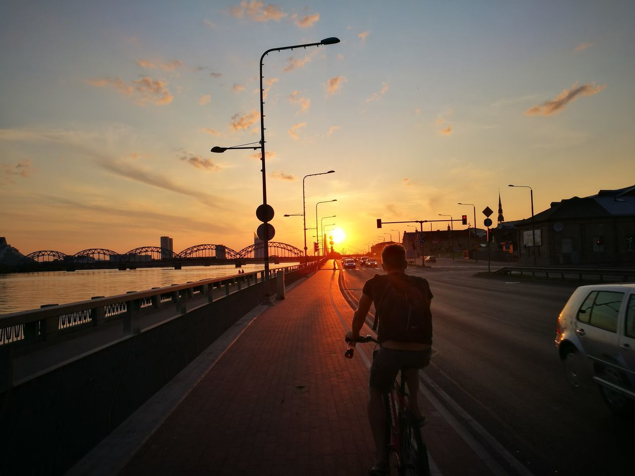 sunset, transportation, sky, land vehicle, mode of transport, cloud - sky, road, built structure, architecture, car, real people, bridge - man made structure, street light, street, city, bicycle, outdoors, full length, water, nature, men, building exterior, one person, day, people