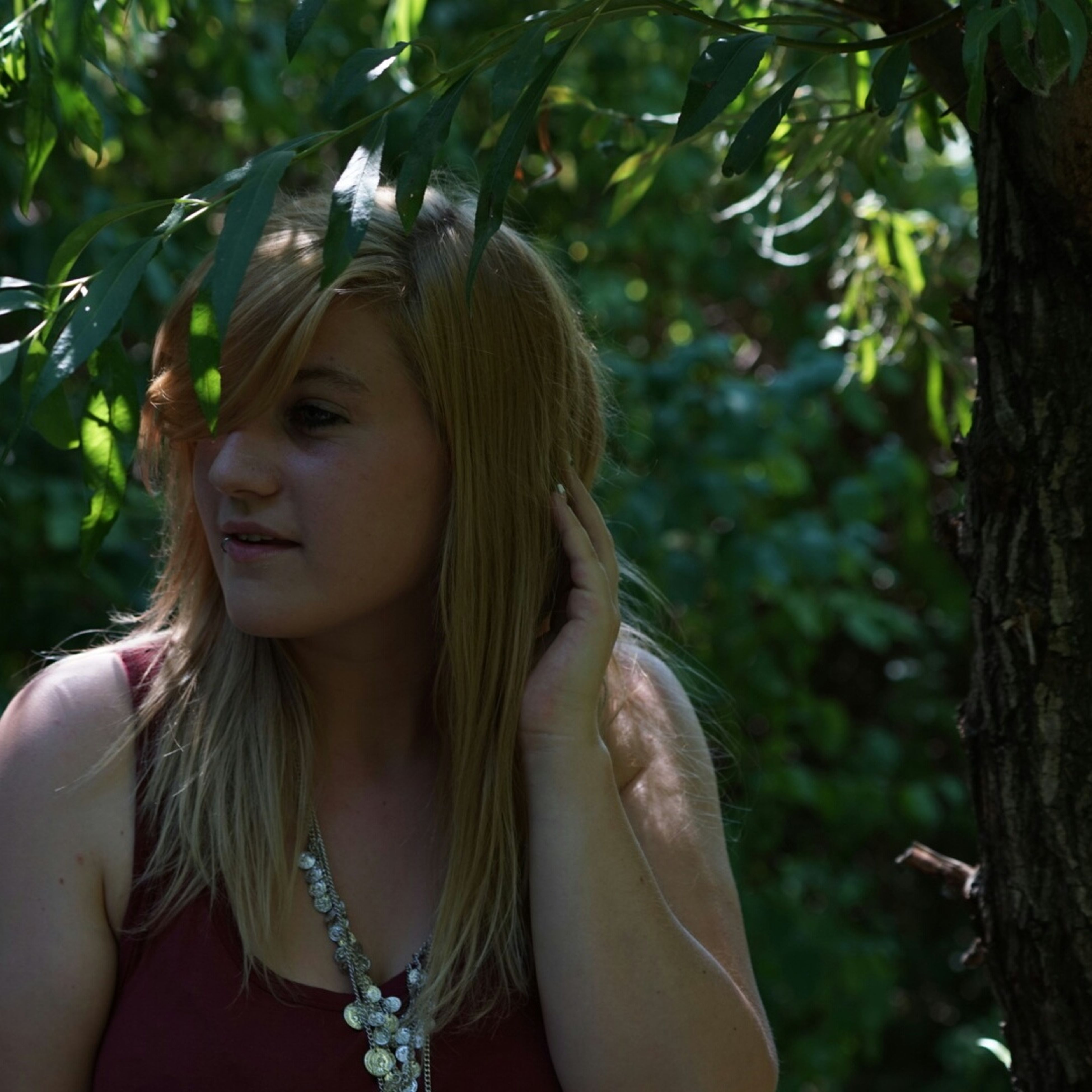 young adult, young women, focus on foreground, lifestyles, person, tree, long hair, leisure activity, headshot, portrait, front view, looking at camera, casual clothing, smiling, close-up, day, park - man made space