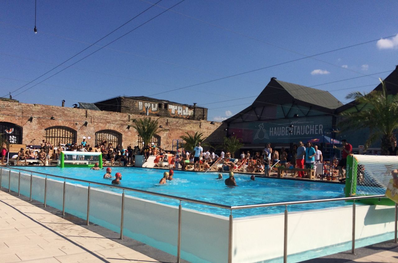 large group of people, real people, swimming pool, water, men, built structure, outdoors, building exterior, day, architecture, leisure activity, lifestyles, women, clear sky, sky, people