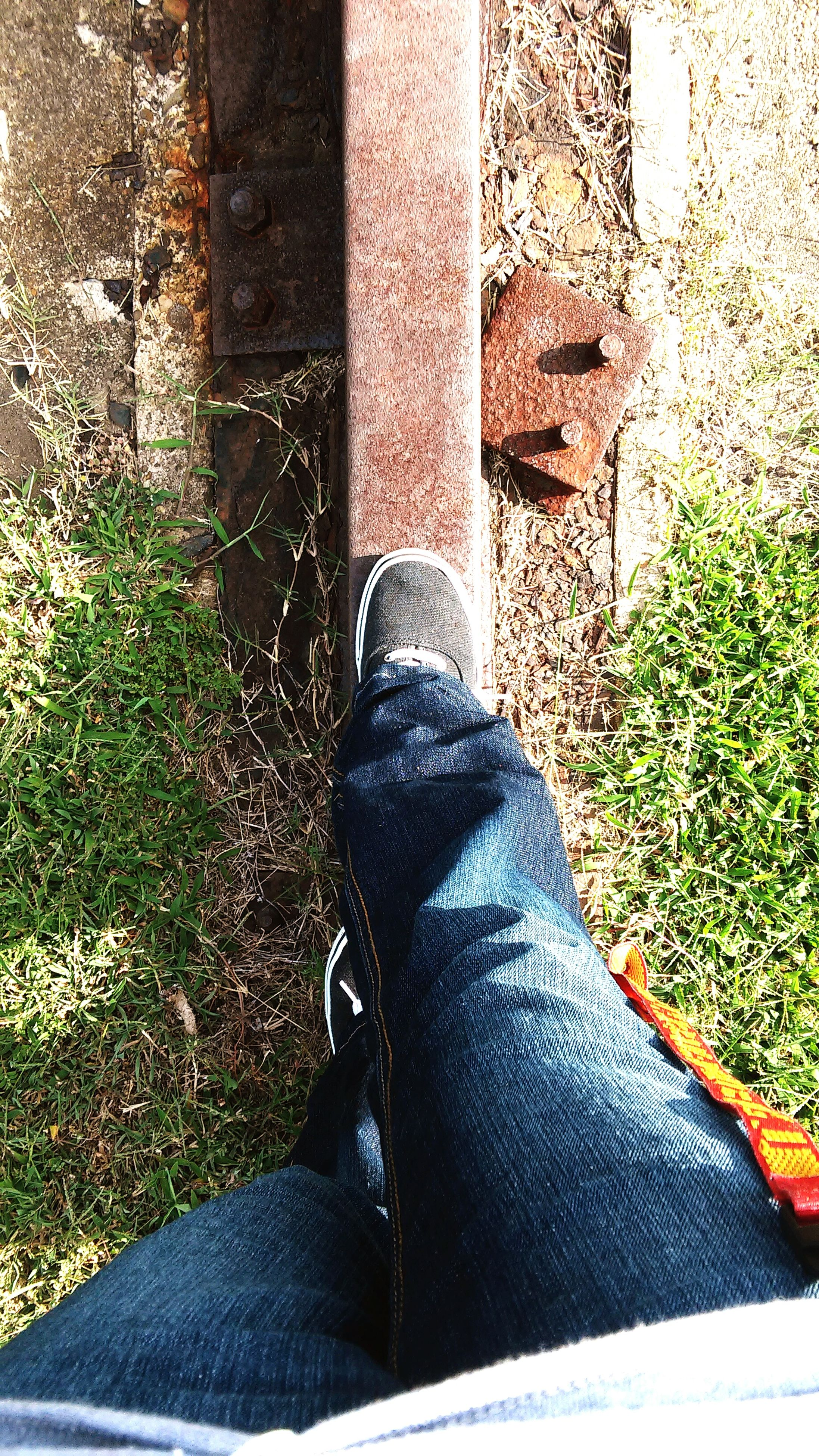 low section, person, lifestyles, personal perspective, shoe, standing, day, sunlight, outdoors, footpath, high angle view, leisure activity, jeans, unrecognizable person, grass, sidewalk