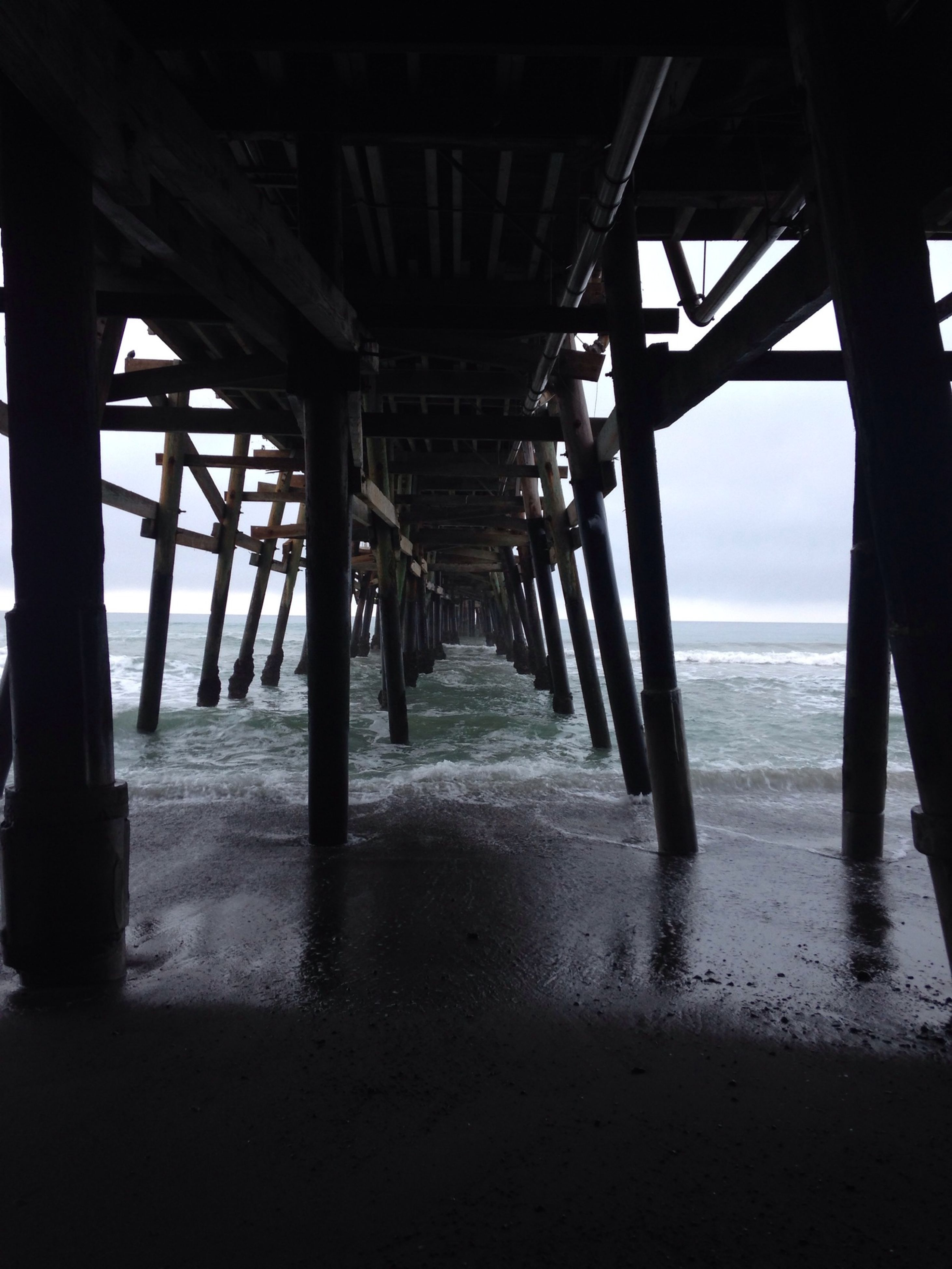 built structure, sea, architectural column, architecture, water, indoors, the way forward, diminishing perspective, beach, column, support, horizon over water, sky, pier, below, bridge - man made structure, in a row, connection, long, vanishing point
