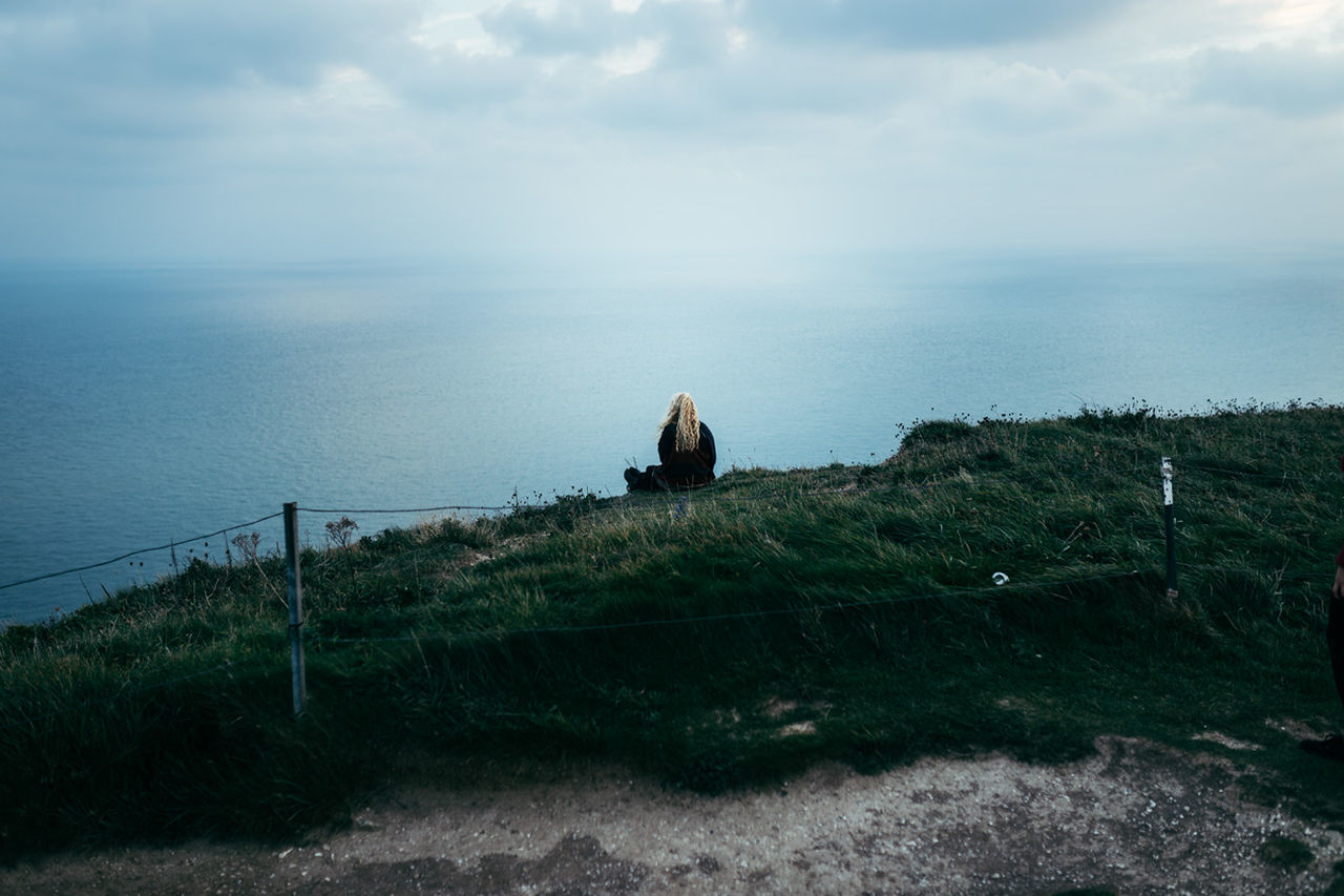 sea, horizon over water, water, nature, sky, scenics, tranquil scene, tranquility, beauty in nature, day, outdoors, cloud - sky, grass, one person, people