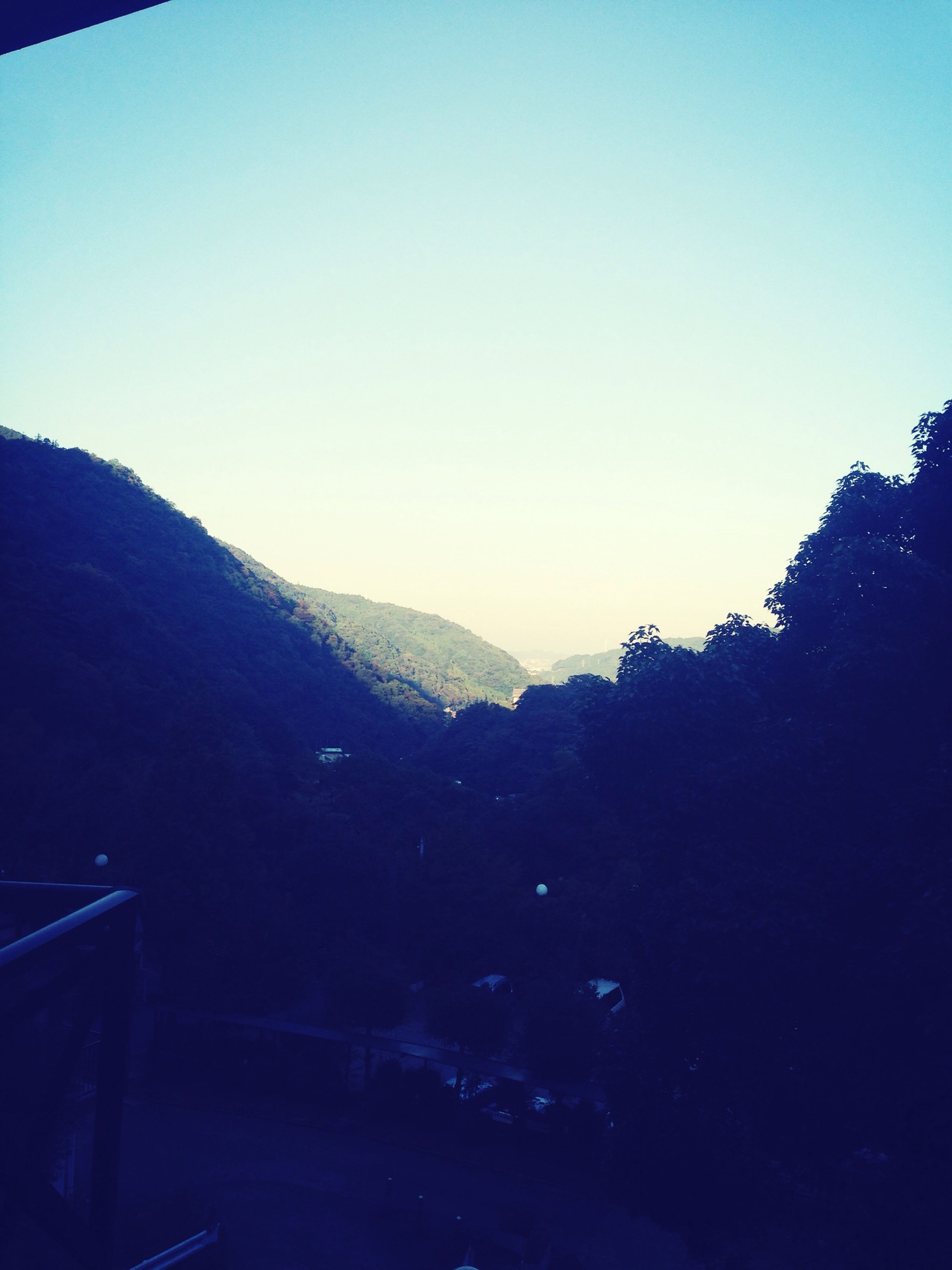 clear sky, mountain, copy space, tranquility, tree, scenics, tranquil scene, beauty in nature, silhouette, blue, mountain range, nature, landscape, dusk, non-urban scene, sky, outdoors, sunset, idyllic, no people