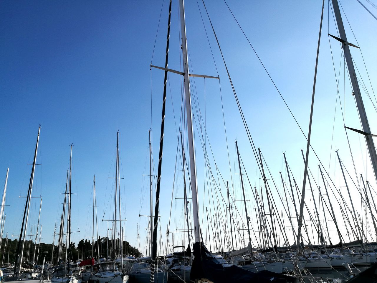 transportation, mode of transport, mast, nautical vessel, outdoors, sky, no people, moored, car, clear sky, land vehicle, blue, day, nature, low angle view, sailboat, built structure, travel destinations, scenics, harbor, building exterior, architecture