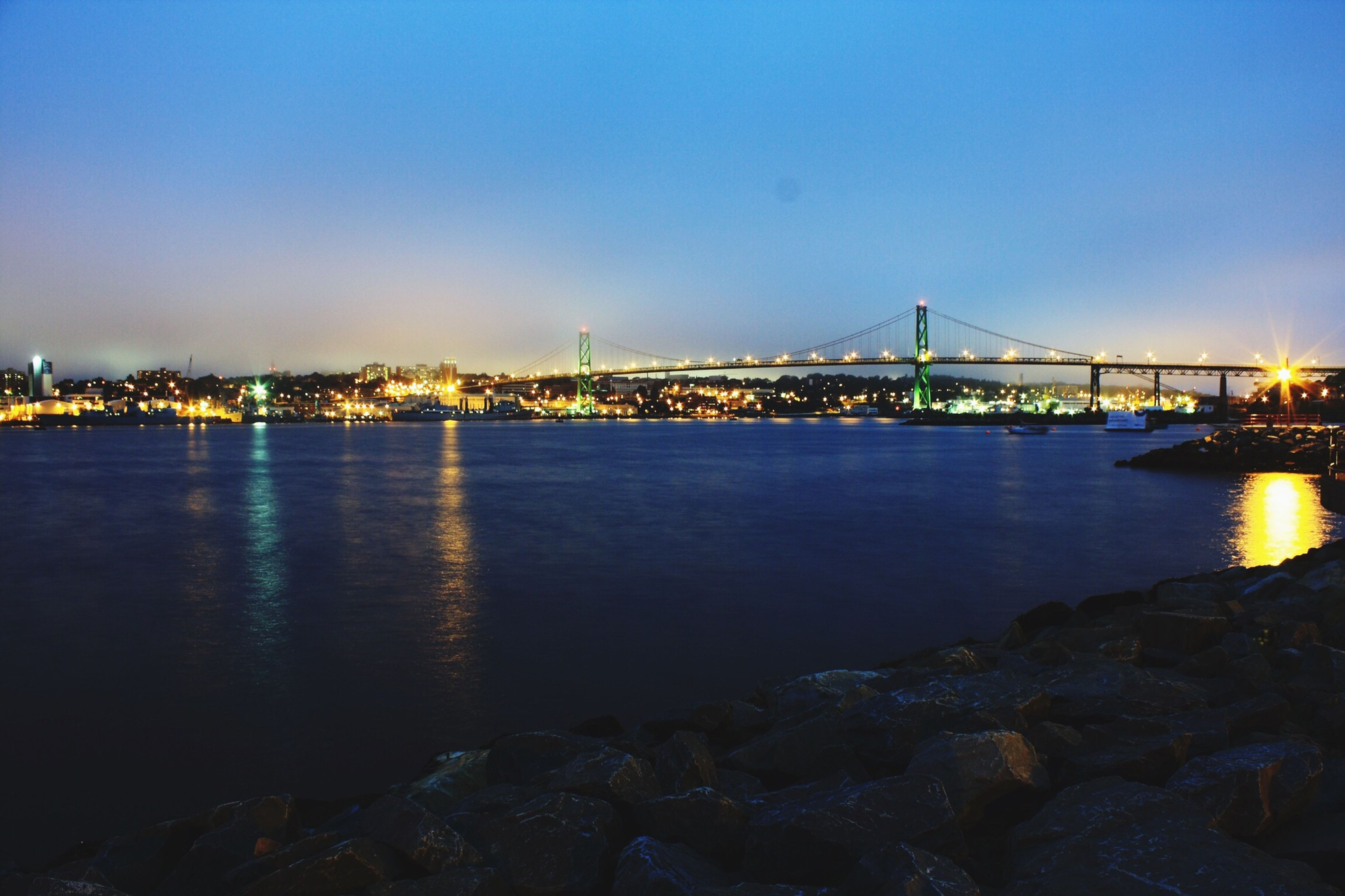 water, illuminated, clear sky, night, copy space, architecture, built structure, connection, sea, blue, reflection, bridge - man made structure, river, waterfront, city, tranquil scene, engineering, scenics, building exterior, bridge