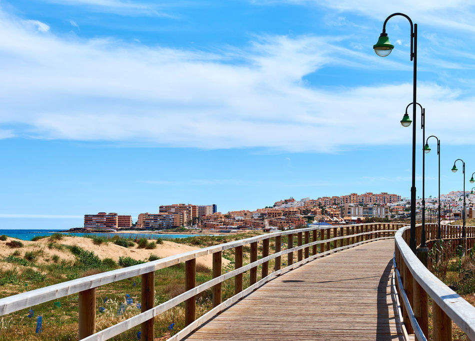 La Mata, Spain - April 4, 2017: People walking along the wooden boardwalk. La Mata is a small town located 5 km northeast of Torrevieja along the Costa Blanca, Province of Alicante. Spain Alicante, Spain City Costa Blanca Dunes Footbridge Footpath La Mata Lanterns Mediterranean Sea Pedestrian Walkway SPAIN Torrevieja Beach Boardwalk Bridge - Man Made Structure Building Exterior Built Structure Landscape Outdoors Seafront Sunny Day Tourist Resort Town Travel Destinations Waterfront