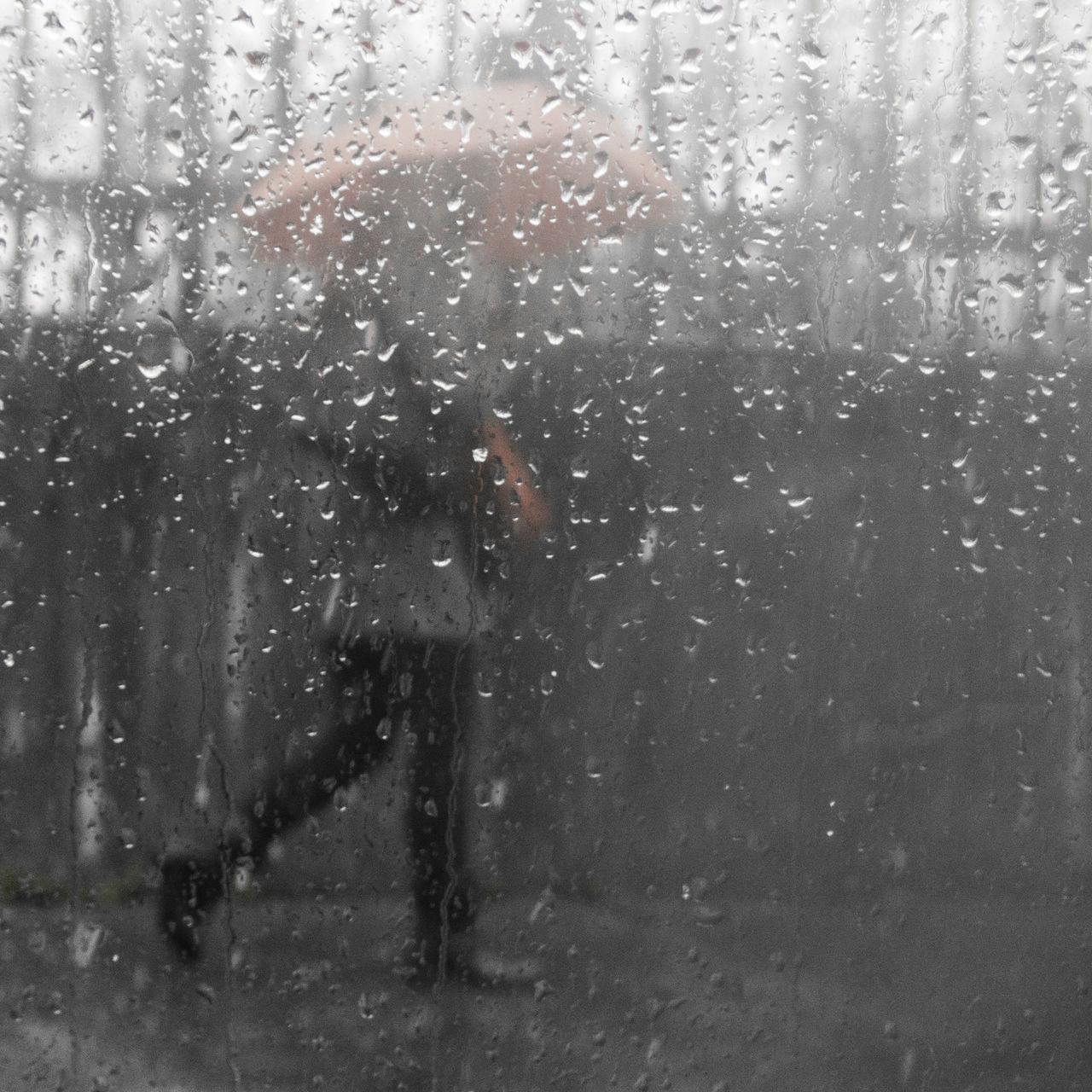 Person Walking On Footpath Seen Through Window Glass During Rainy Season