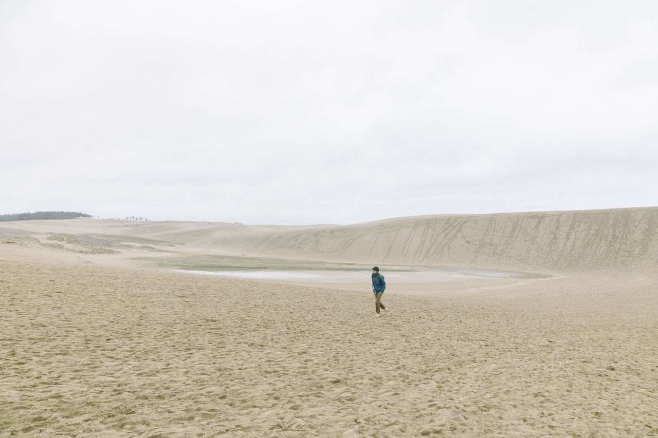 sand, rear view, one person, real people, nature, day, scenics, sky, landscape, men, desert, outdoors, beach, beauty in nature, arid climate, sand dune, one man only, people