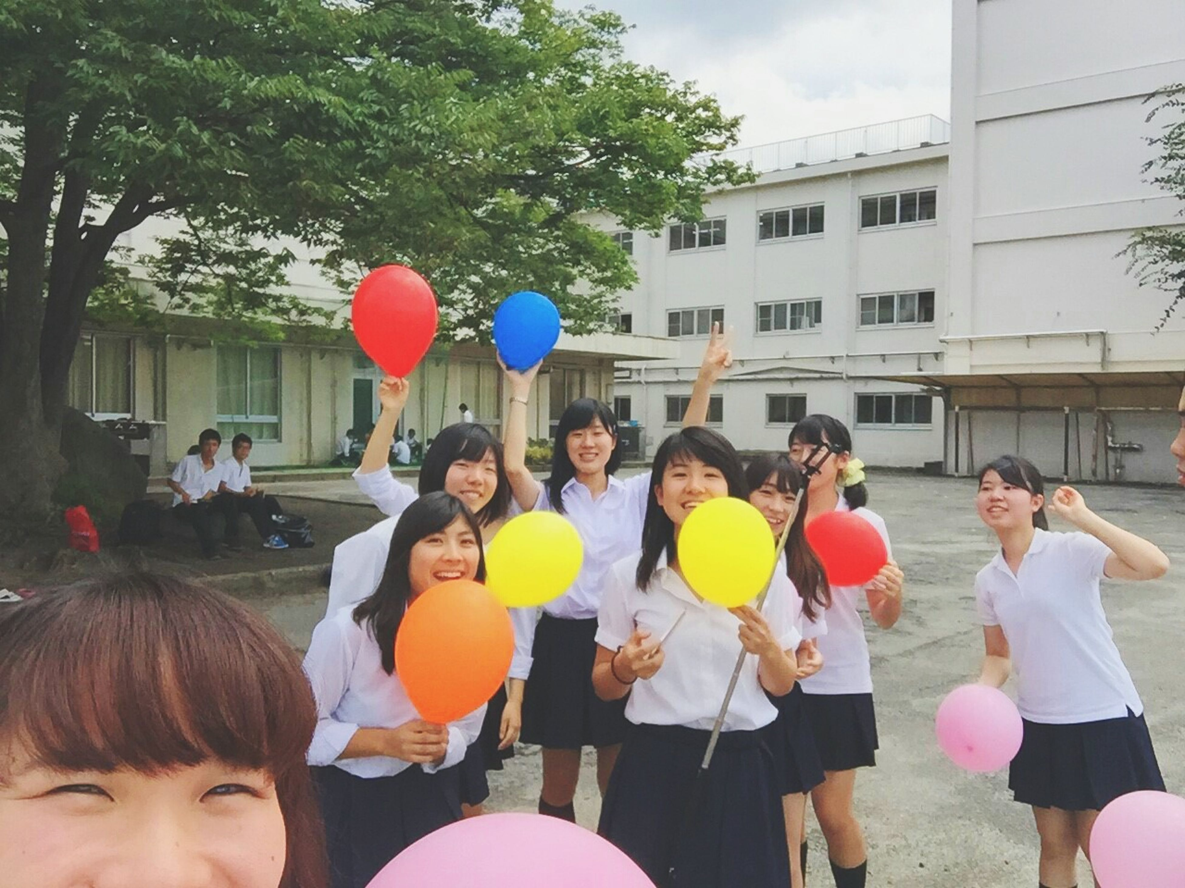 lifestyles, leisure activity, childhood, large group of people, balloon, celebration, enjoyment, girls, togetherness, person, fun, multi colored, tree, boys, playing, elementary age, building exterior, casual clothing, men