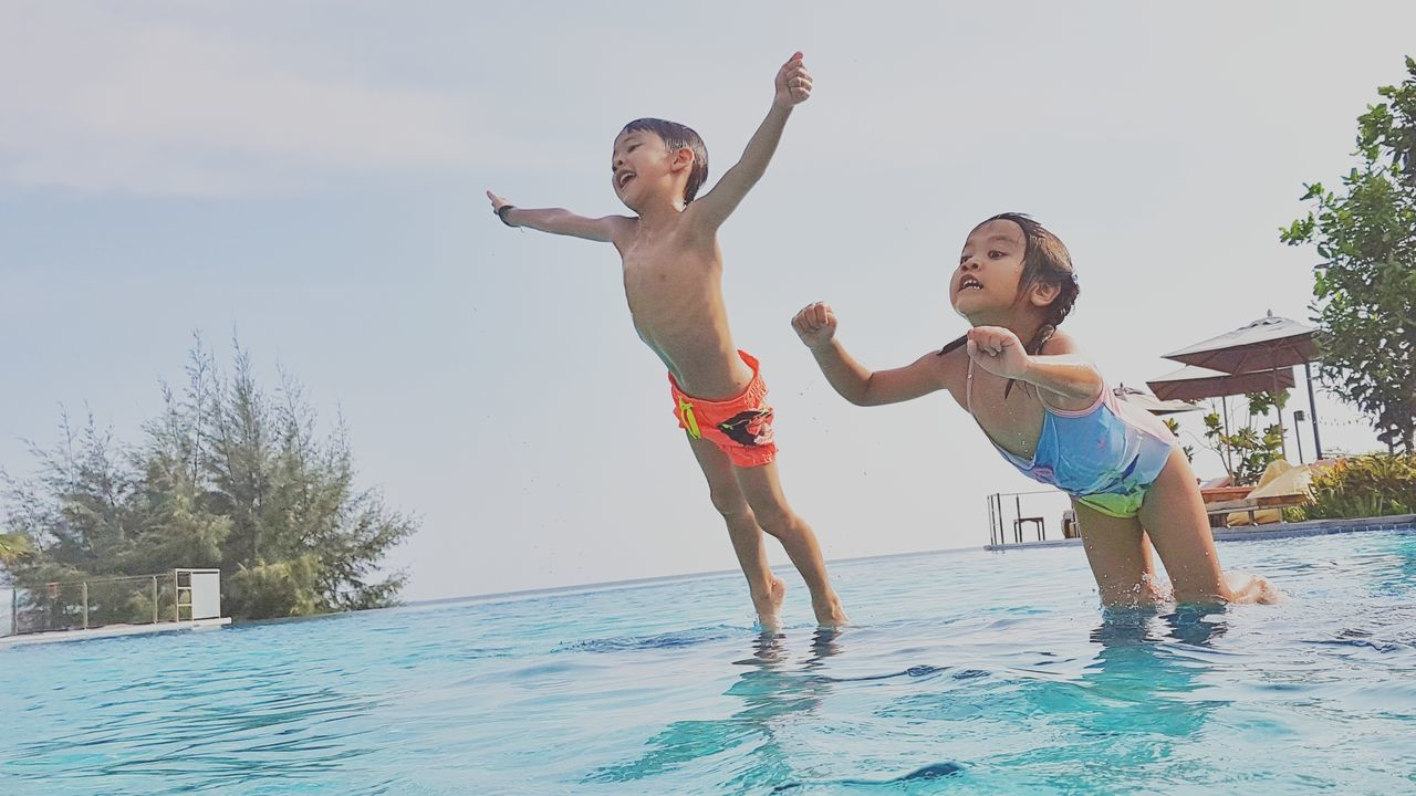 elementary age, leisure activity, boys, real people, childhood, shirtless, lifestyles, water, smiling, togetherness, happiness, outdoors, arms raised, day, family, mid adult men, fun, swimming pool, son, family with one child, jumping, bonding, girls, full length, father, mid-air, cheerful, young adult, sky, nature, vacations, standing, playing, young women, friendship
