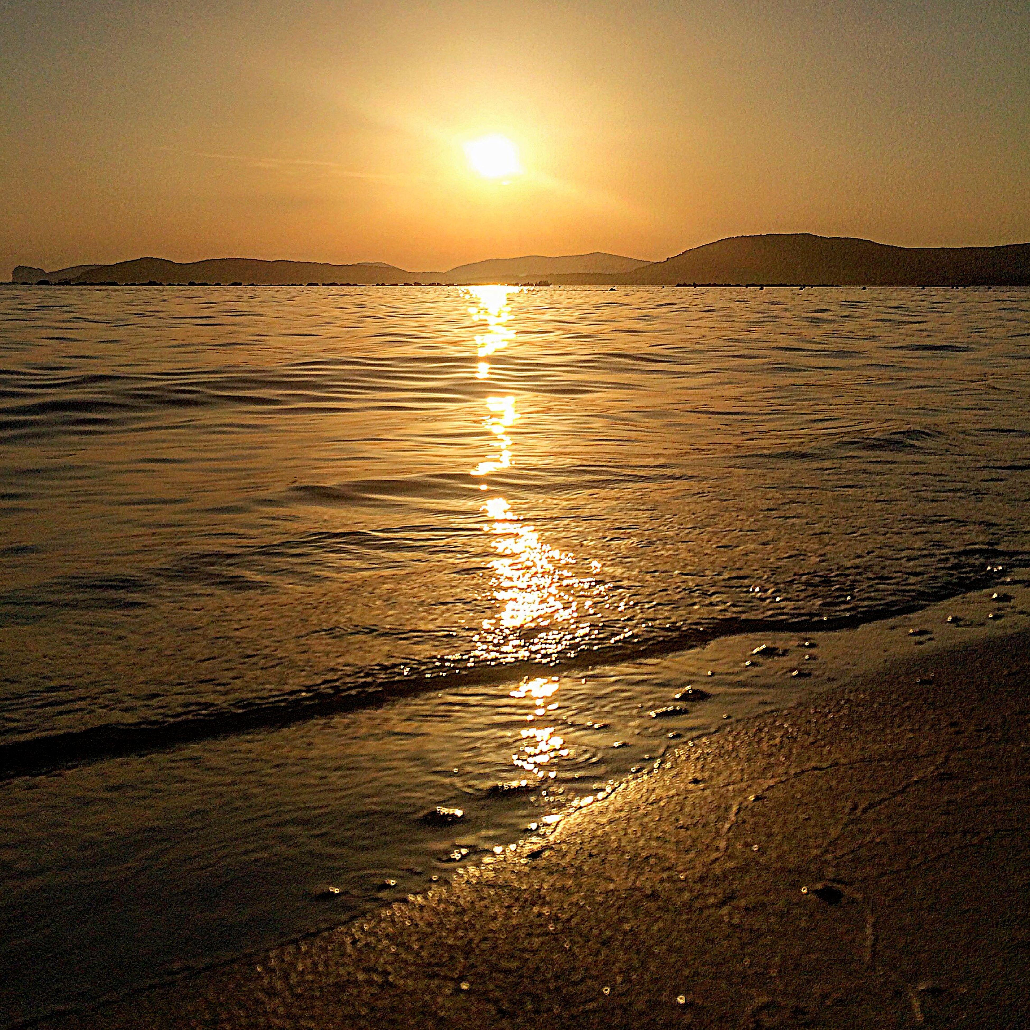 water, sunset, sun, reflection, tranquil scene, scenics, sea, tranquility, beauty in nature, beach, shore, sunlight, nature, orange color, idyllic, sky, silhouette, rippled, sunbeam, sand