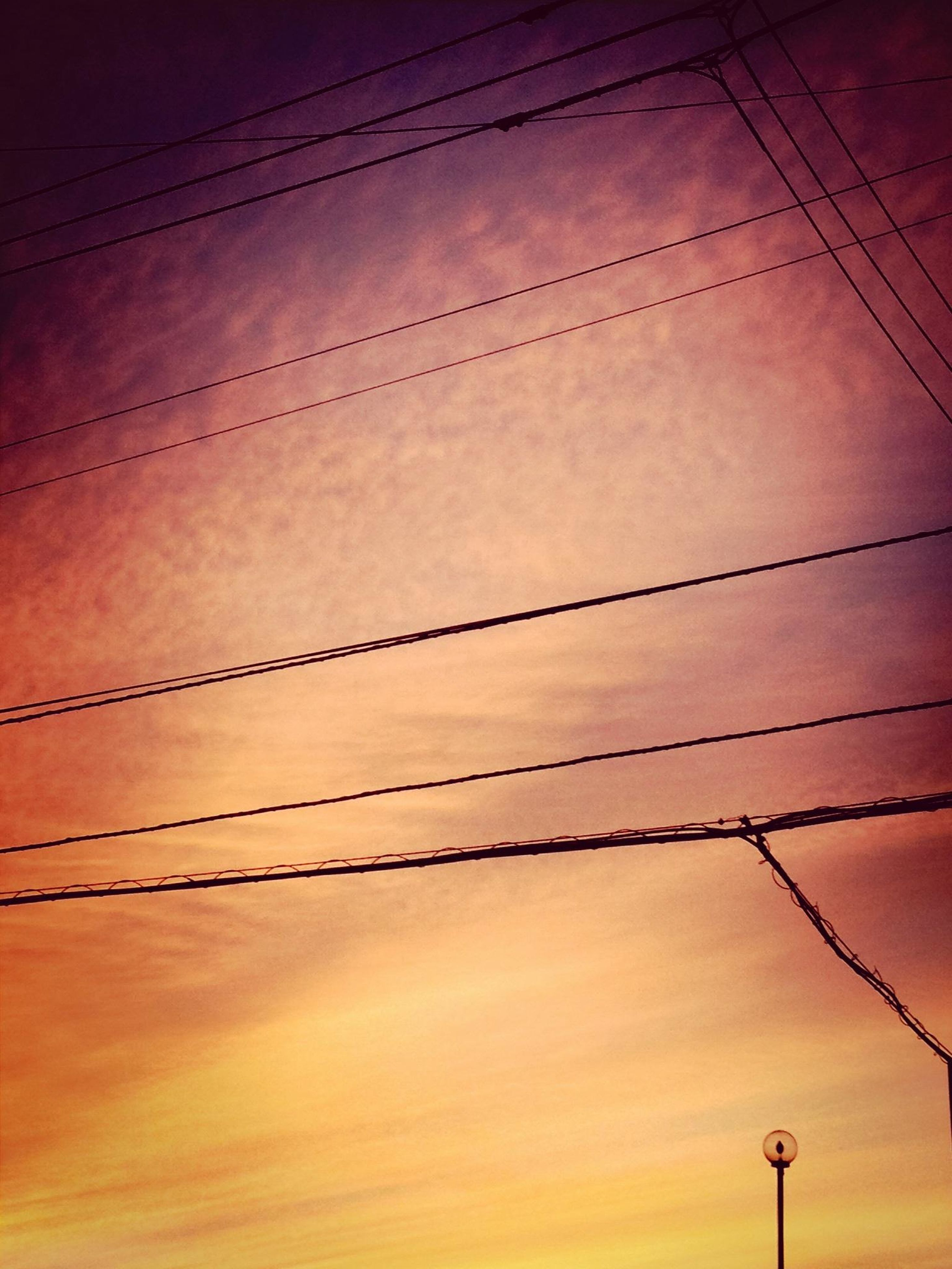 low angle view, power line, cable, electricity, power supply, connection, sky, electricity pylon, fuel and power generation, sunset, silhouette, cloud - sky, technology, power cable, lighting equipment, no people, built structure, outdoors, wire, orange color